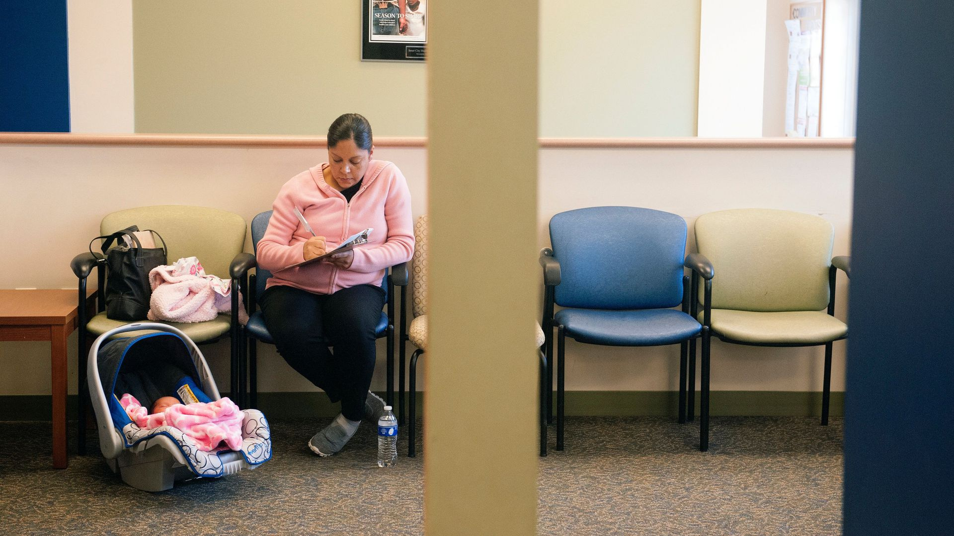 A woman sits in a doctor's office with her infant filling out paperwork.