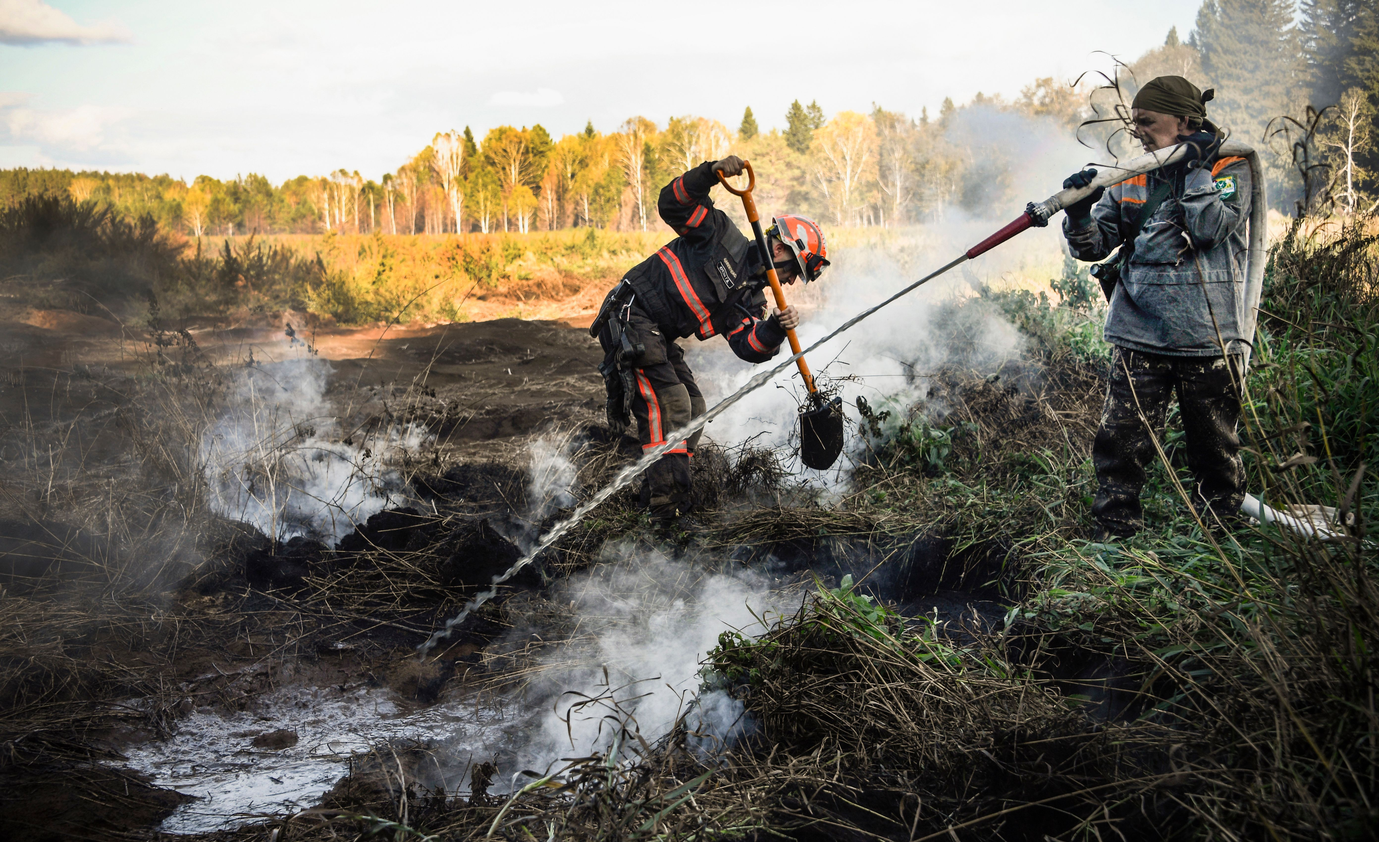 Greenpeace and local activists extinguish a peat fire in a Suzunsky forest next to the village of Shipunovo, 170 kms south from Siberian city of Novosibirsk on September 11