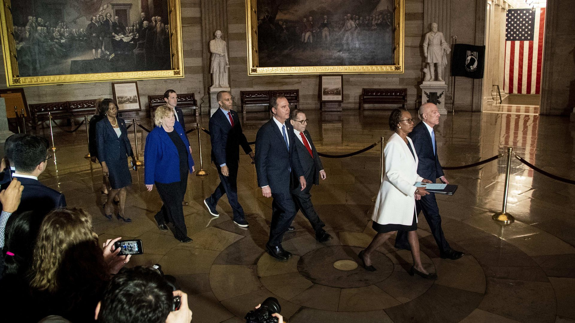House managers walk through the Capitol Rotunda