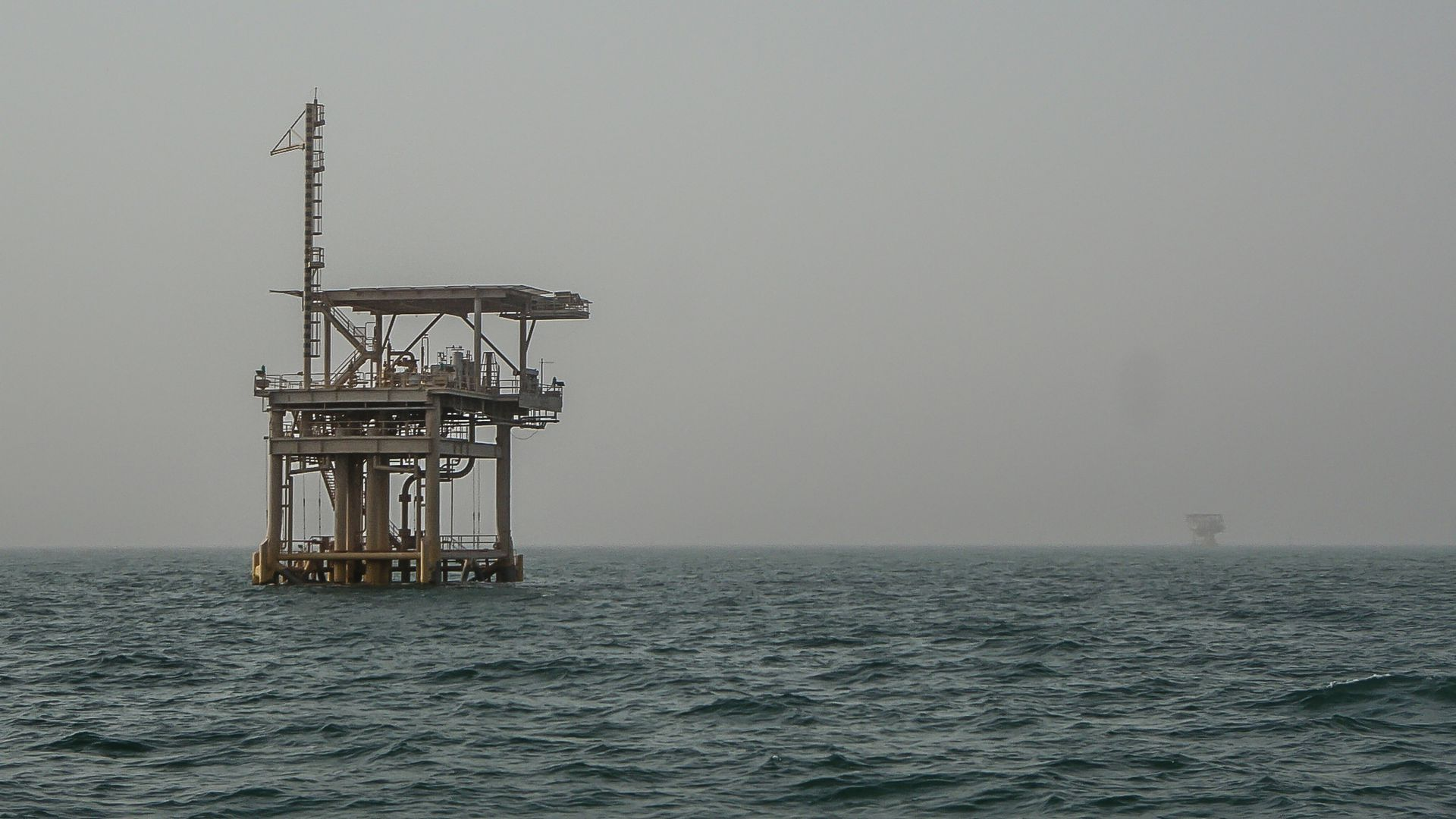 In this image, an oil rig sits in the ocean off the coast of Saudi Arabia.