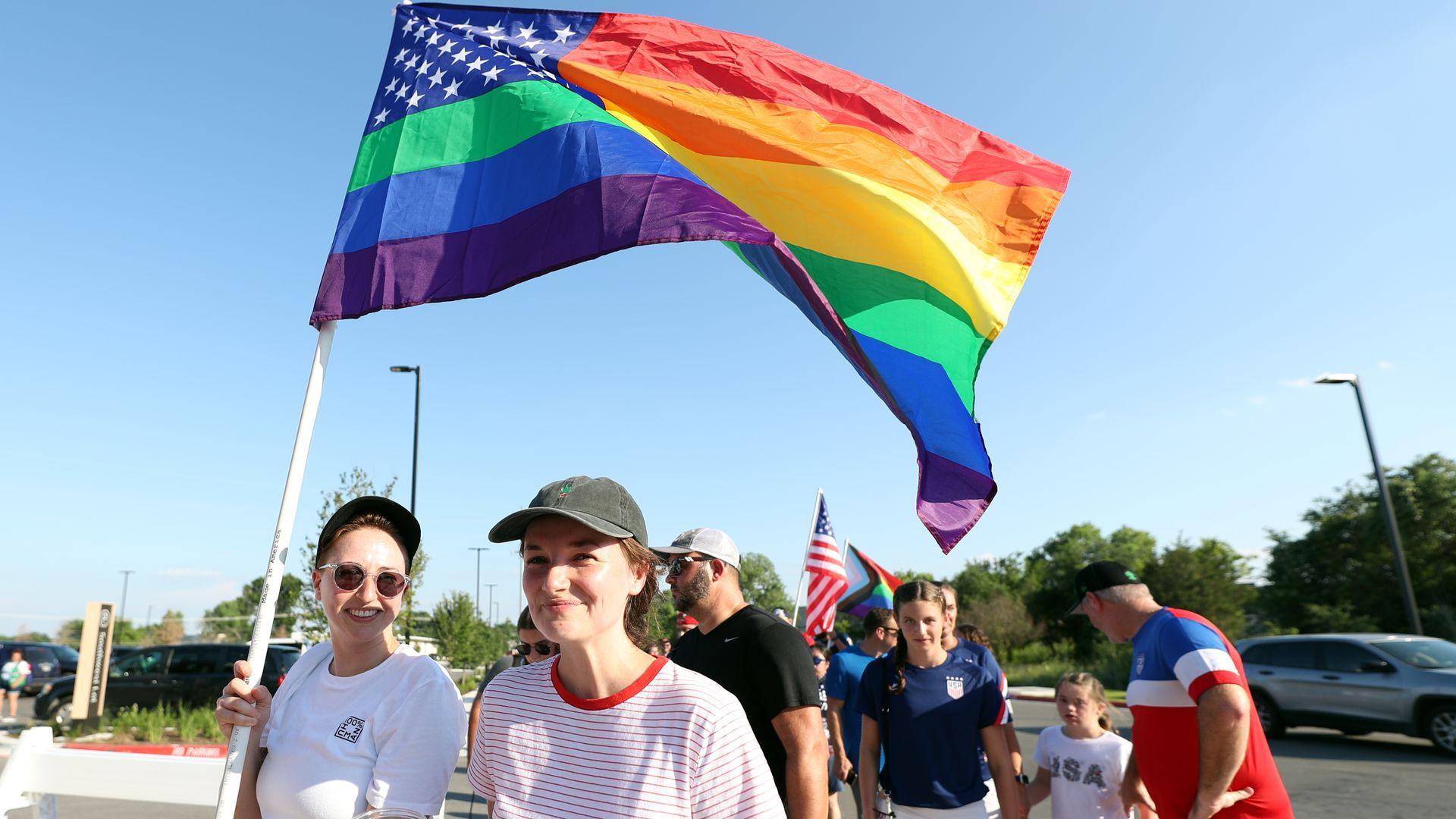 A soccer fan holds a rainbow flag