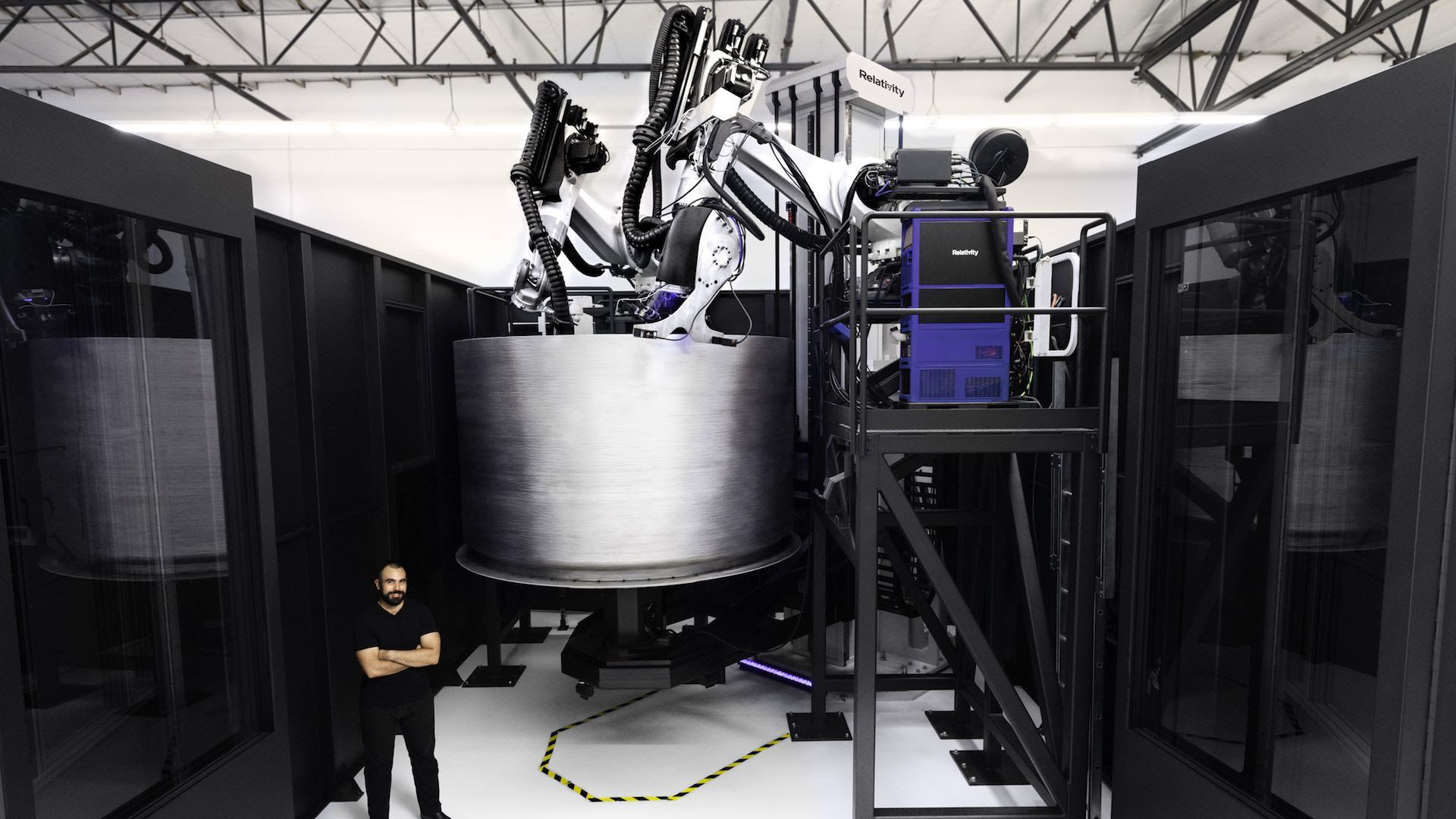 A man stands in front of a metal space device around twice his size.