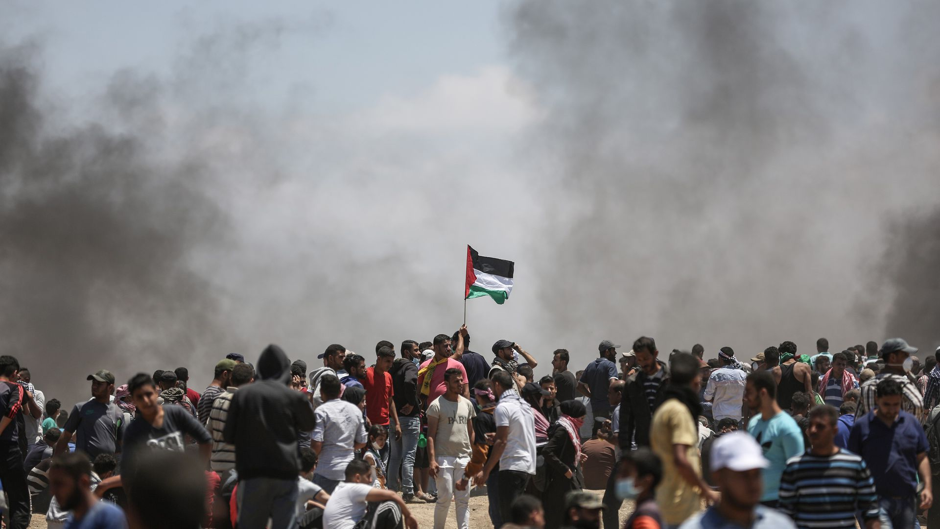 protesters along Gaza border with smoke in background