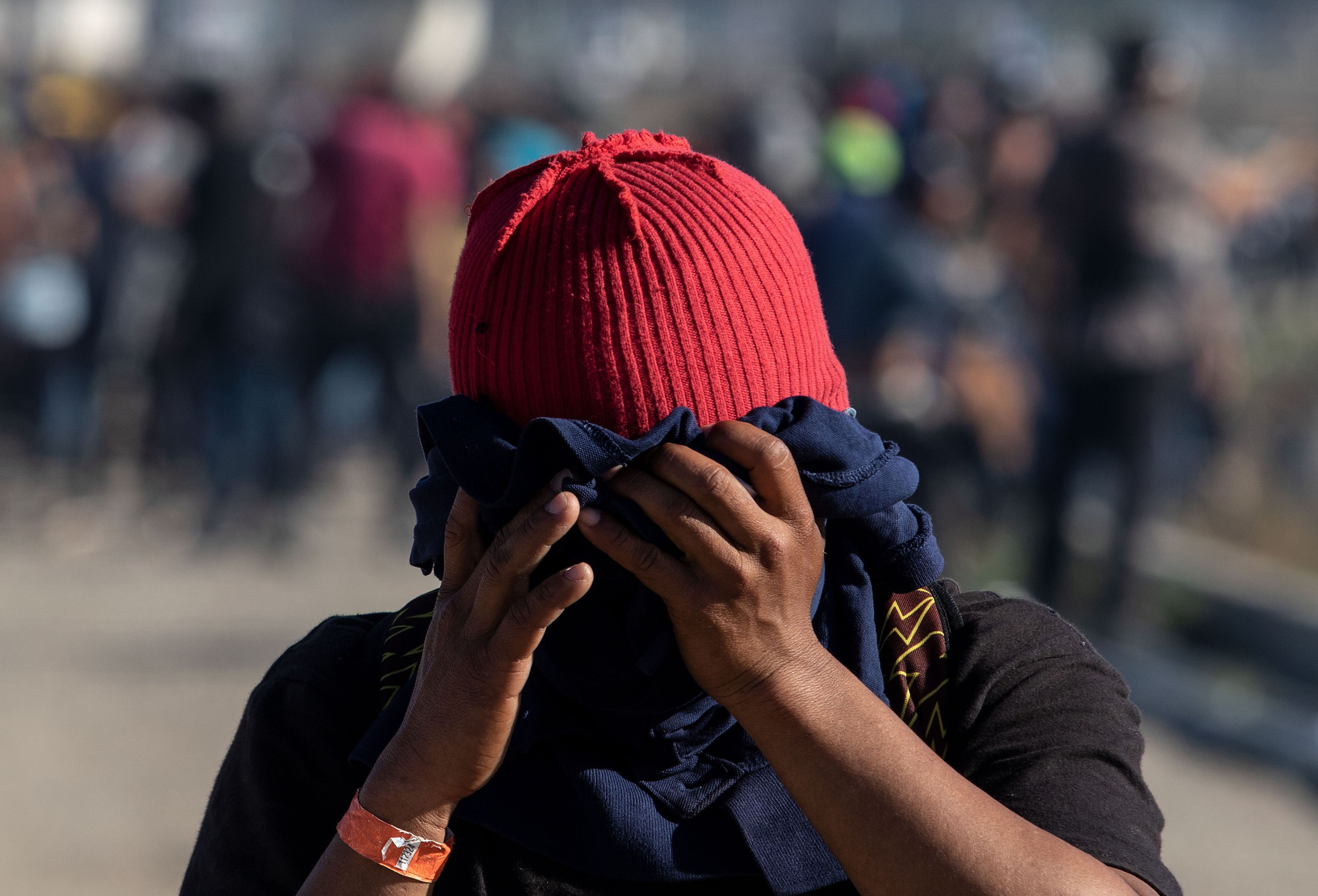 A migrant wearing a red hat and covering their face
