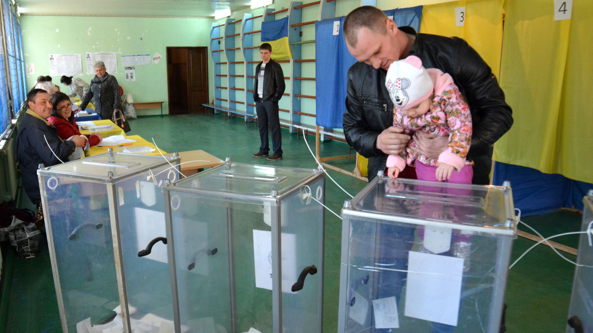 A man with his daughter casting his vote at a Ukrainian polling station