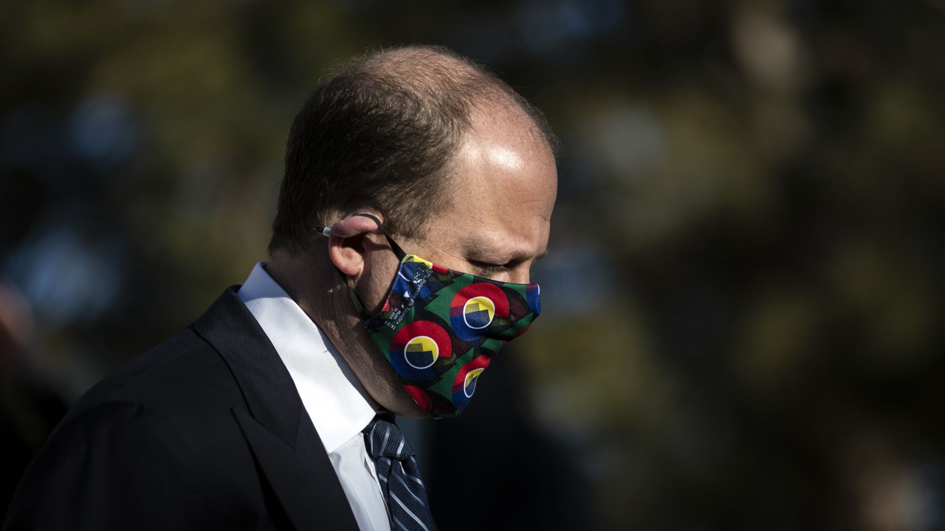 Photo of Jared Polis in a black suit and a face mask that displays the Colorado seal