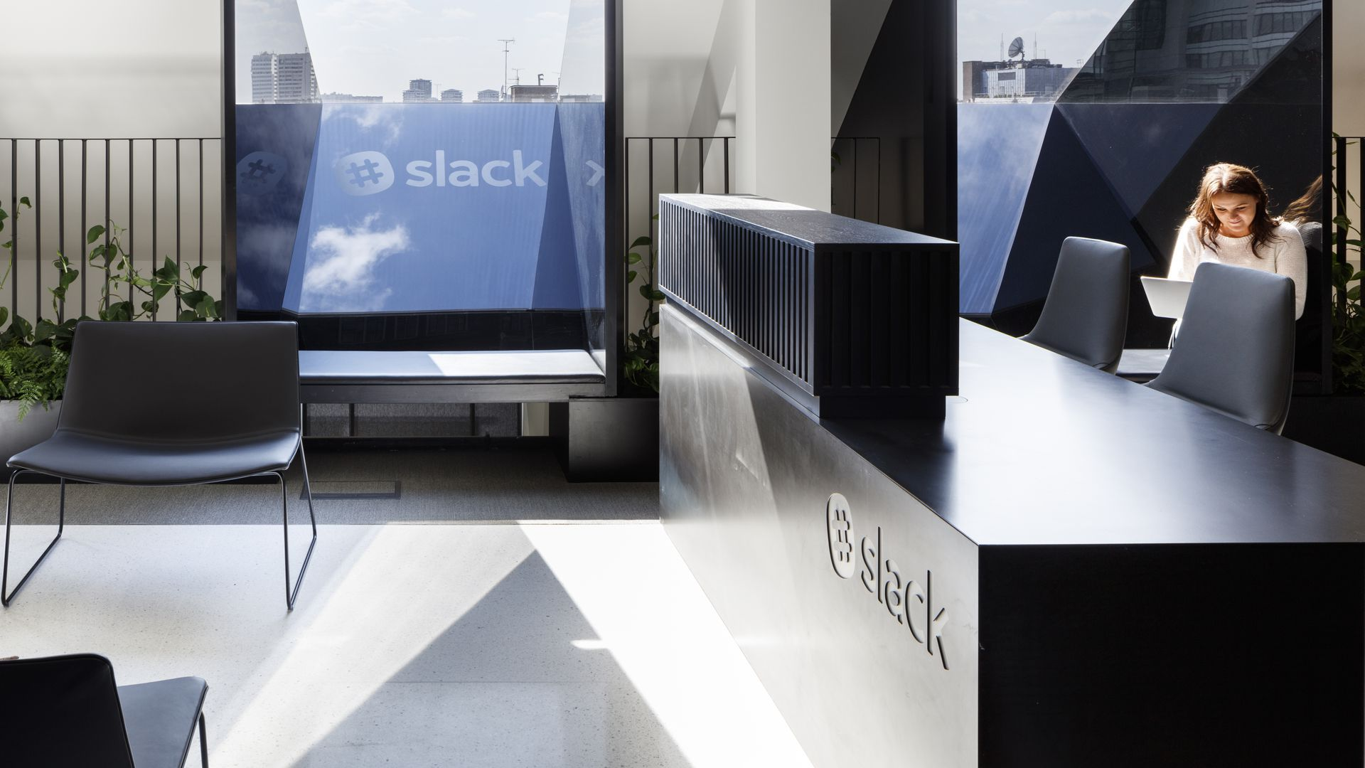 Office lobby of Slack. With woman sitting at a desk and a TV on.