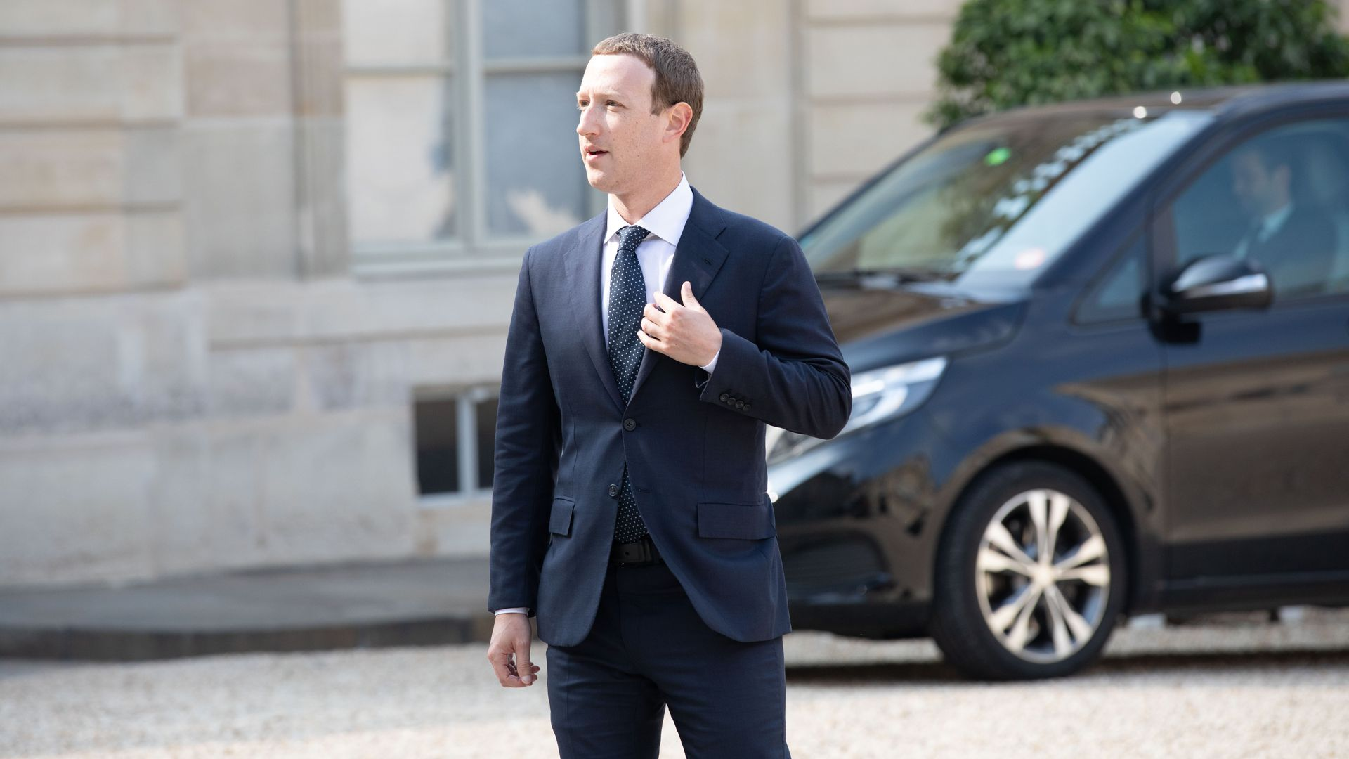 Mark Zuckerberg stands outside in a suit