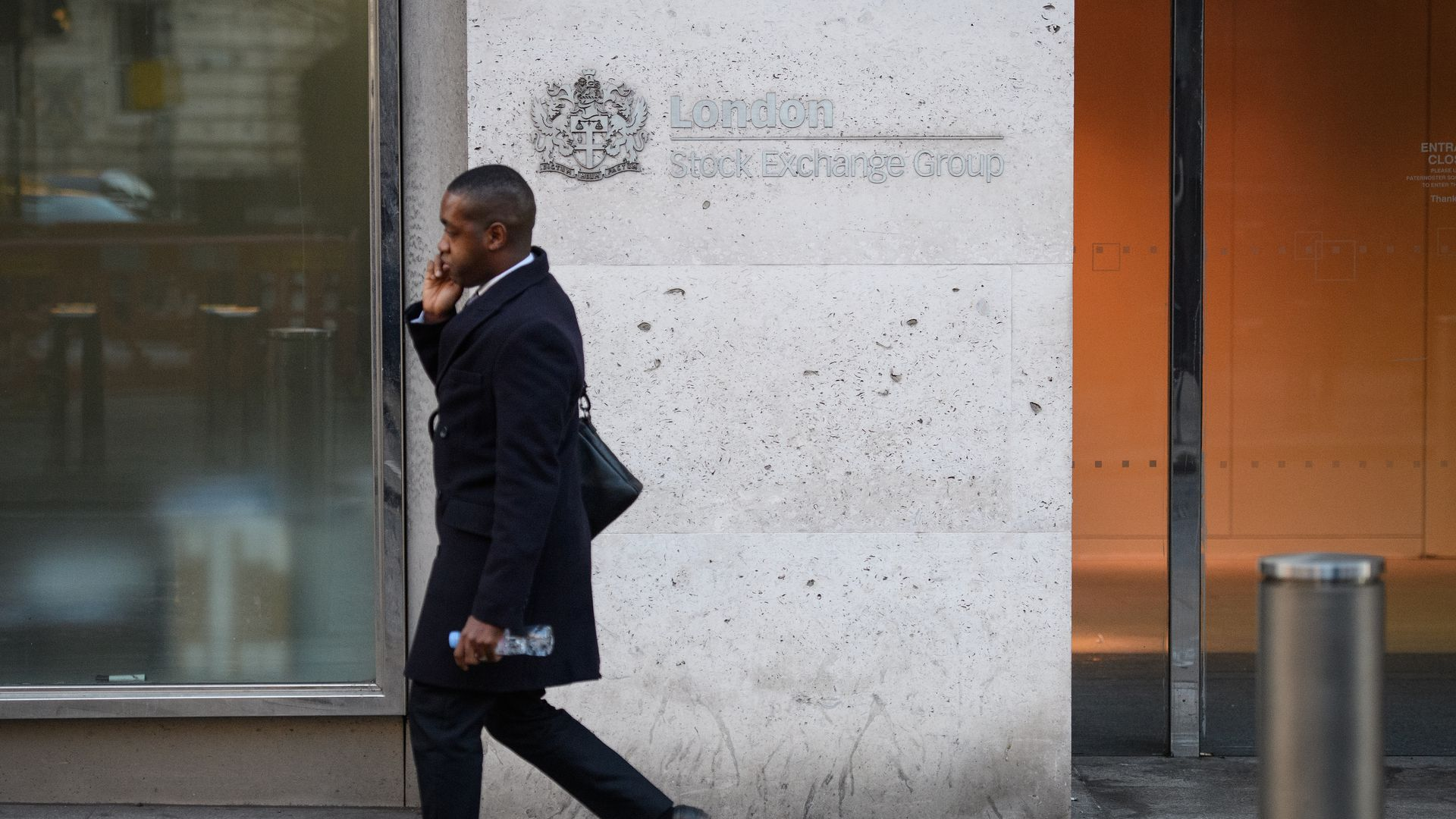 A man walking in front of the London Stock Exchange building