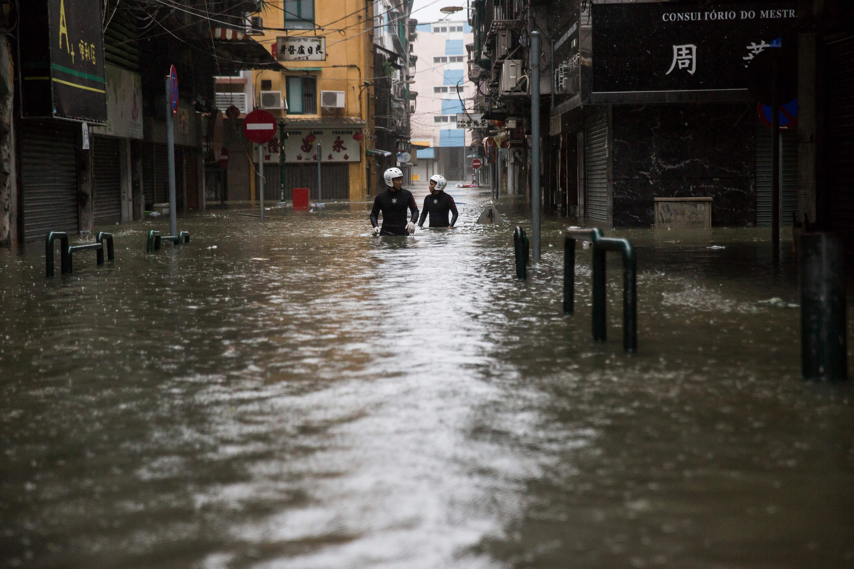 Residents walk through a flooded street in Macau