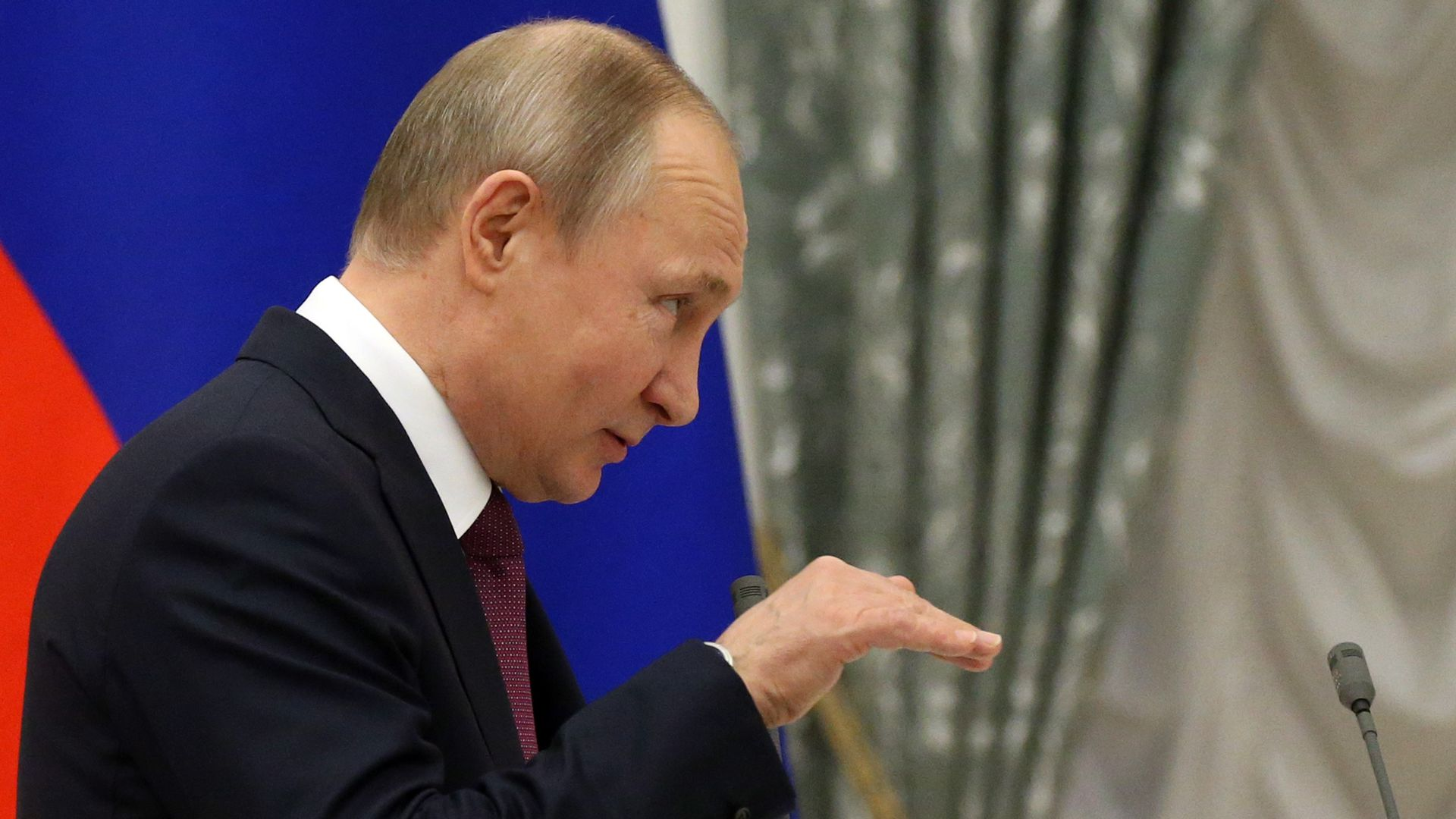 Vladimir Putin gestures with his hand.