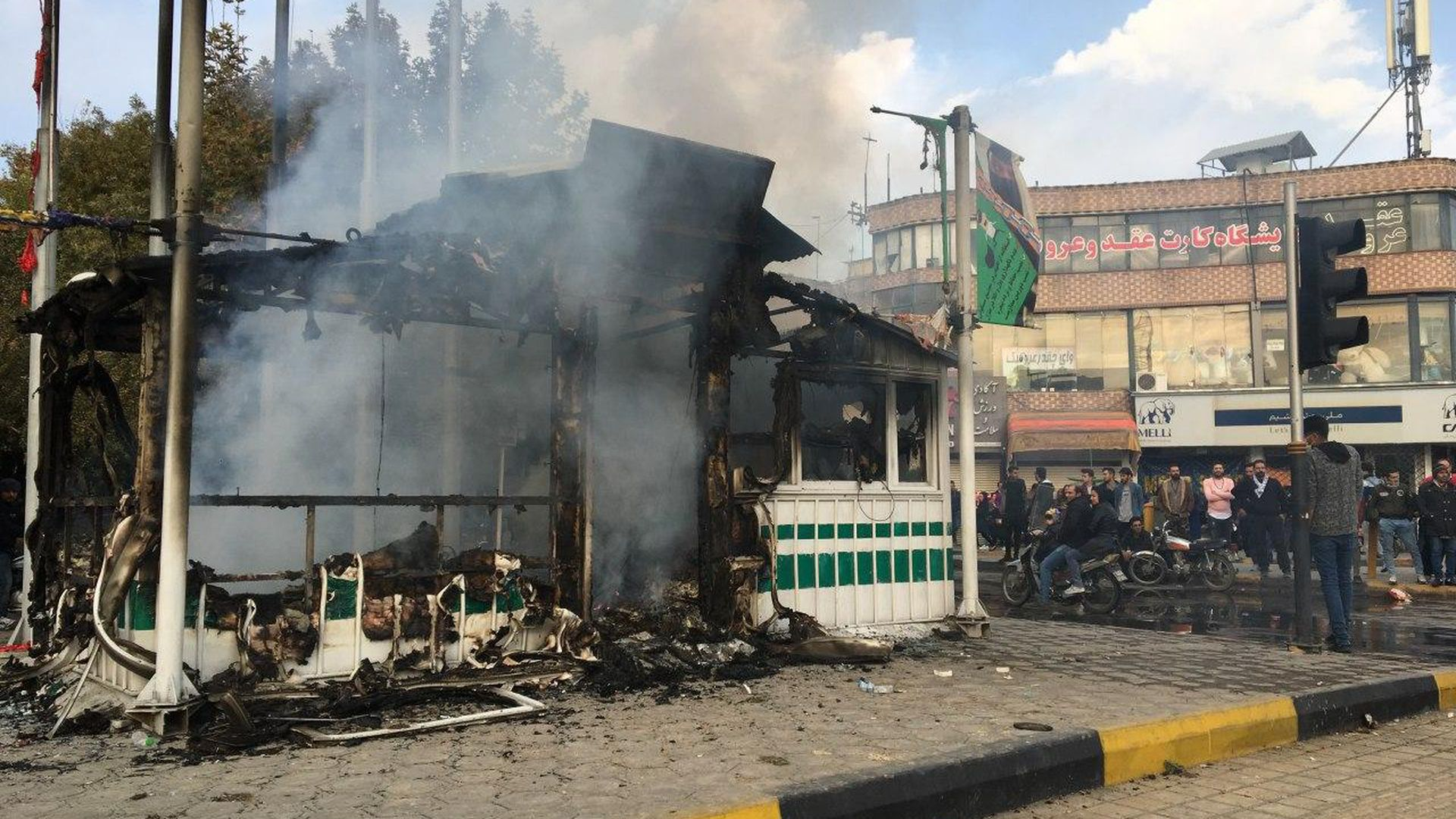 Iranians gather around a charred police station while they protest
