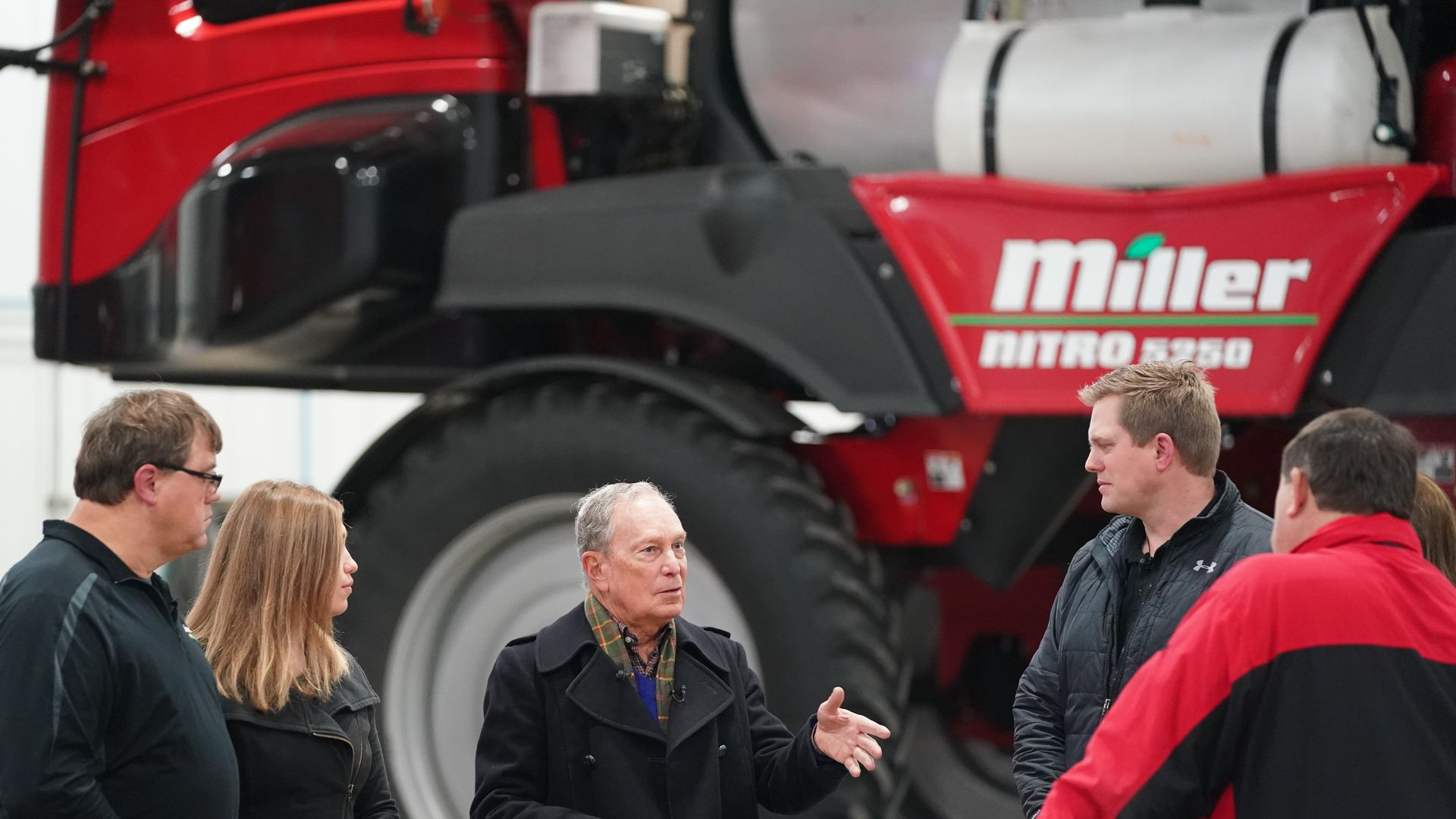 Michael Bloomberg talks to farmers in front of agricultural equipment