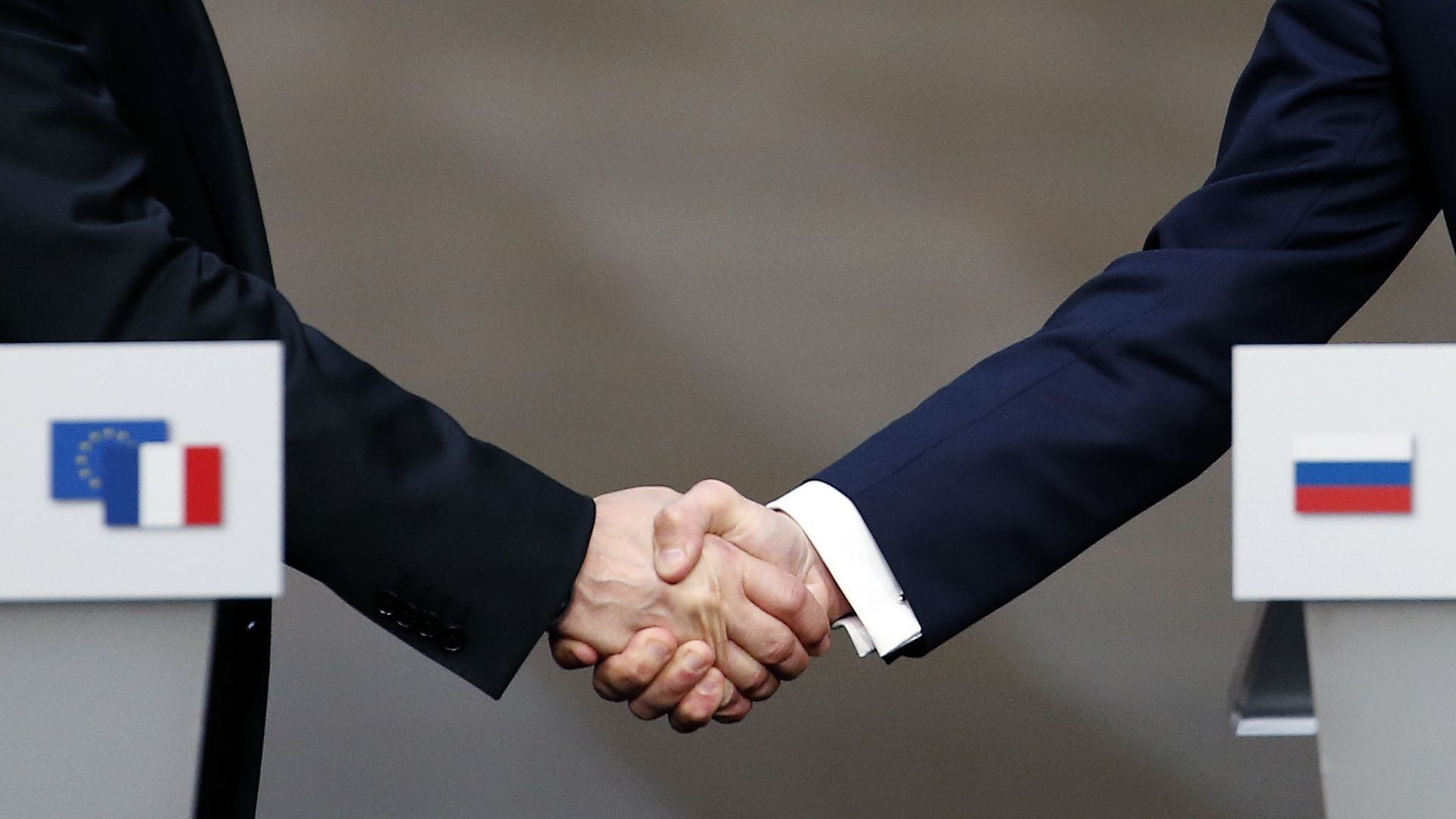 Putin's hand and Macron's hand during a handshake.
