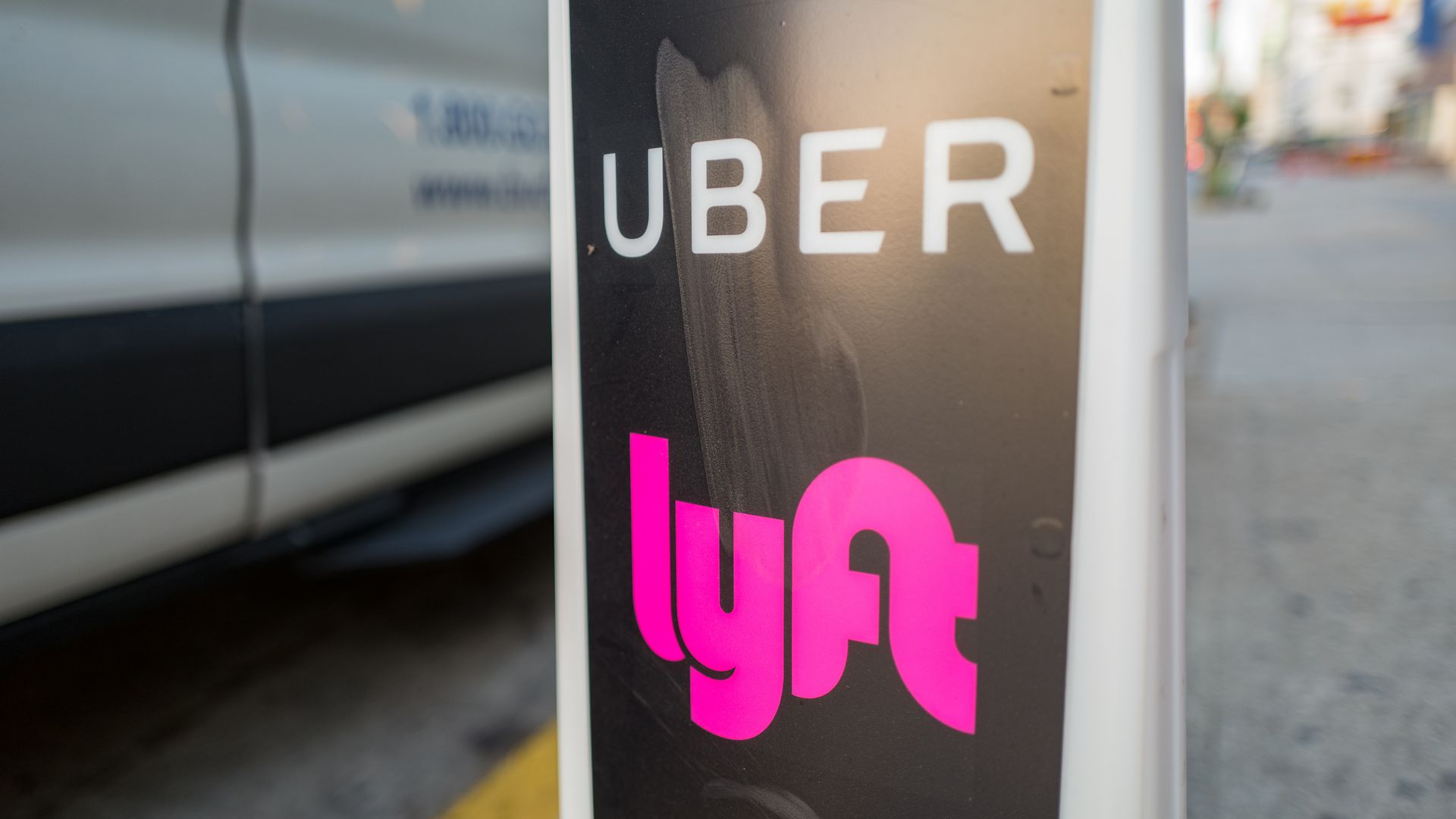 In this image, the Uber and Lyft logos are stacked on top of one another on a pole