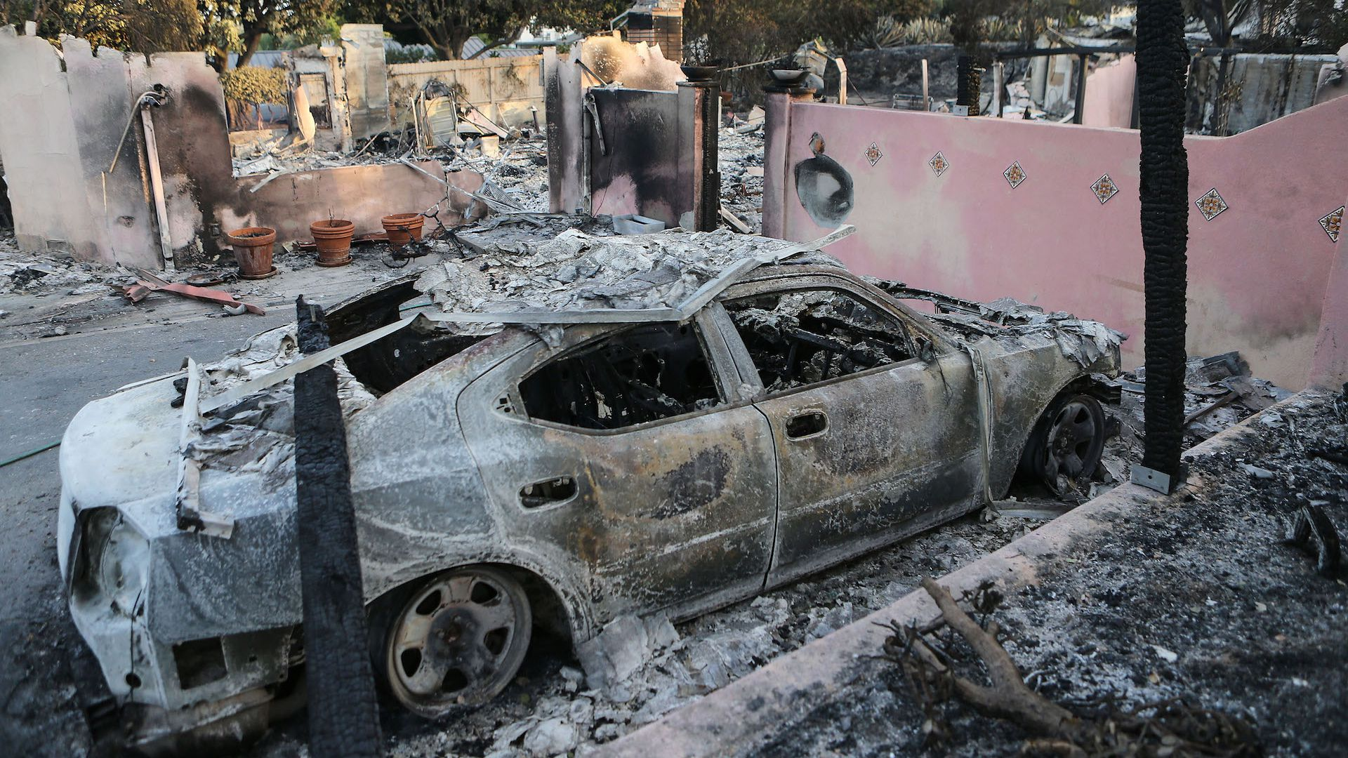 The remains of a destroyed car stand in front of a destroyed home in the aftermath of the Holiday Fire on July 7, 2018 in Goleta, California.