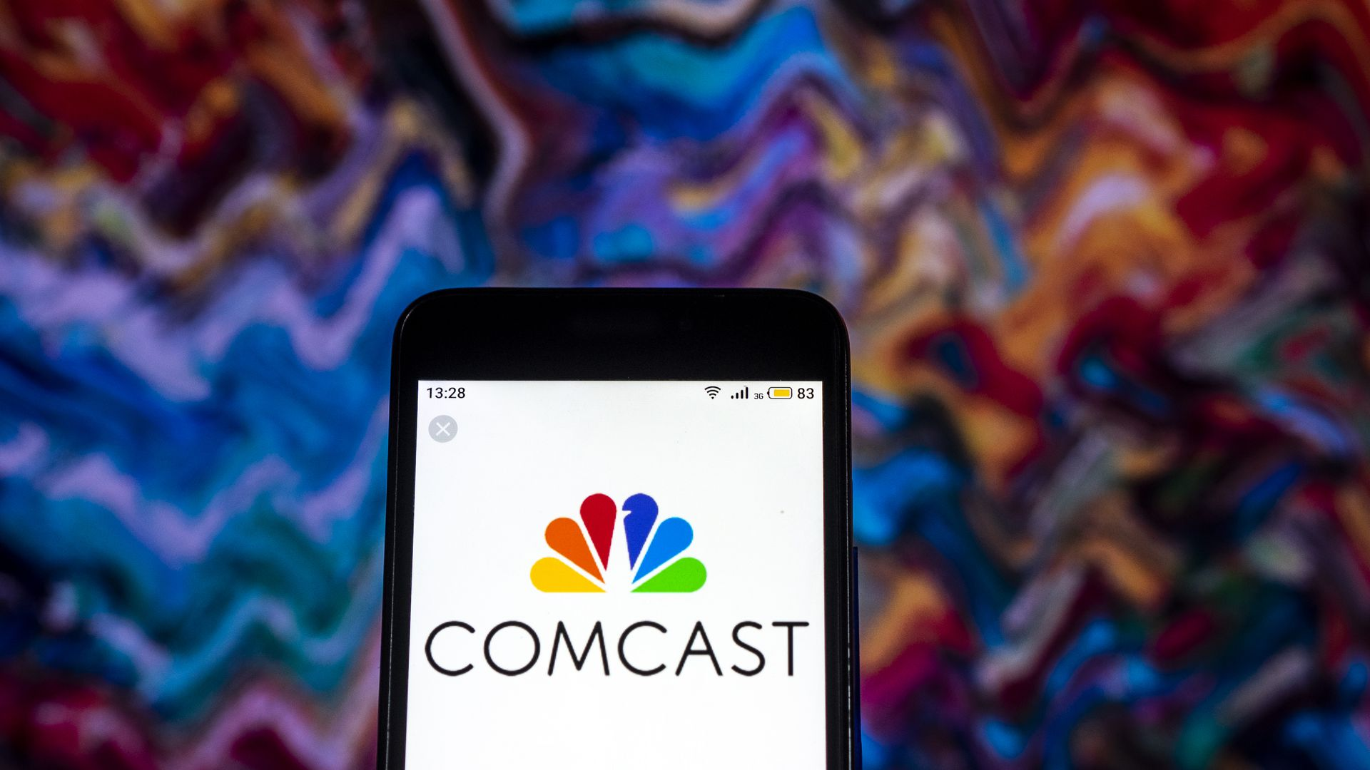 In this image, a phone with the Comcast logo is held up against psychedelic background.