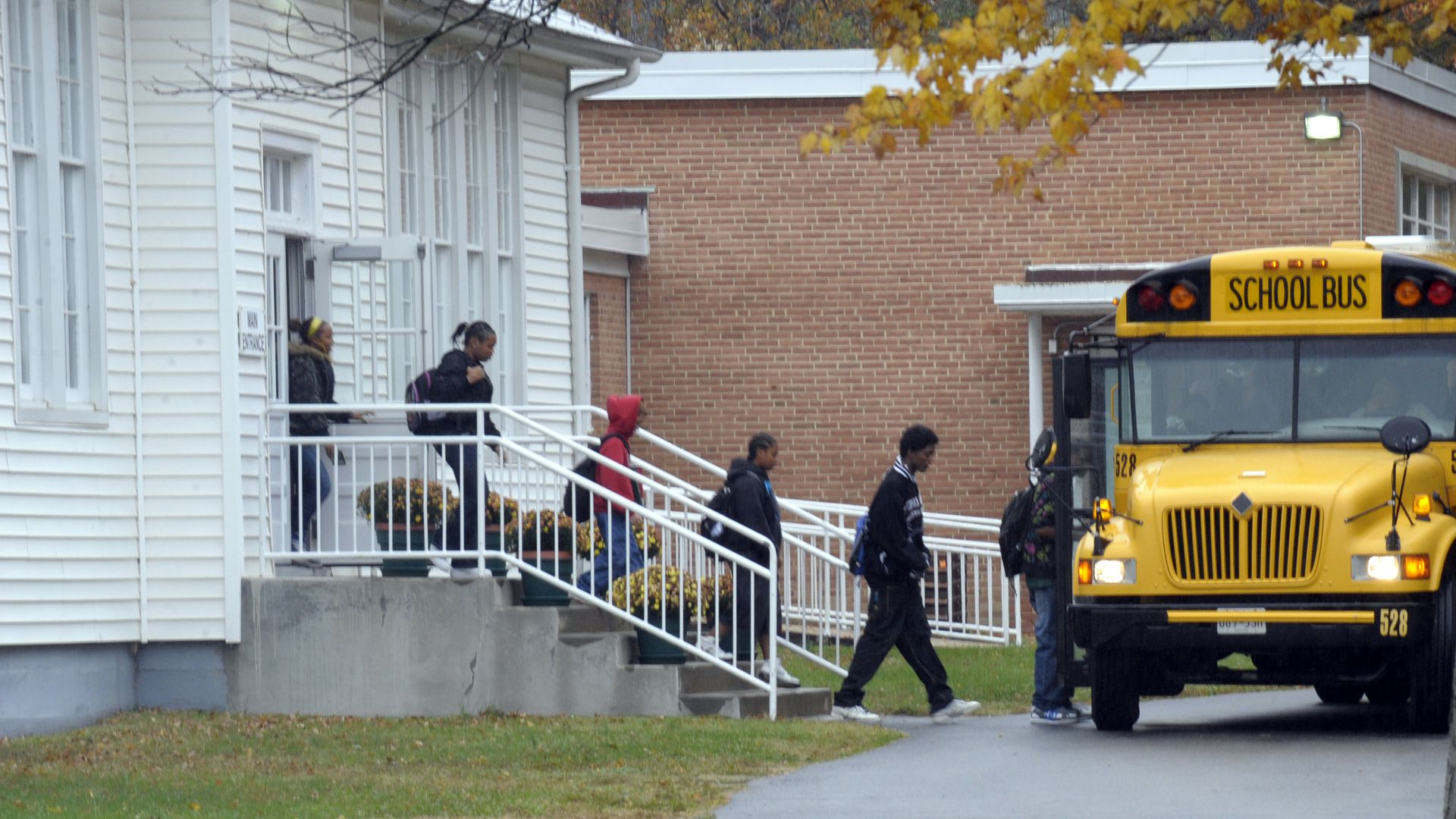 Kids board a yellow school bus