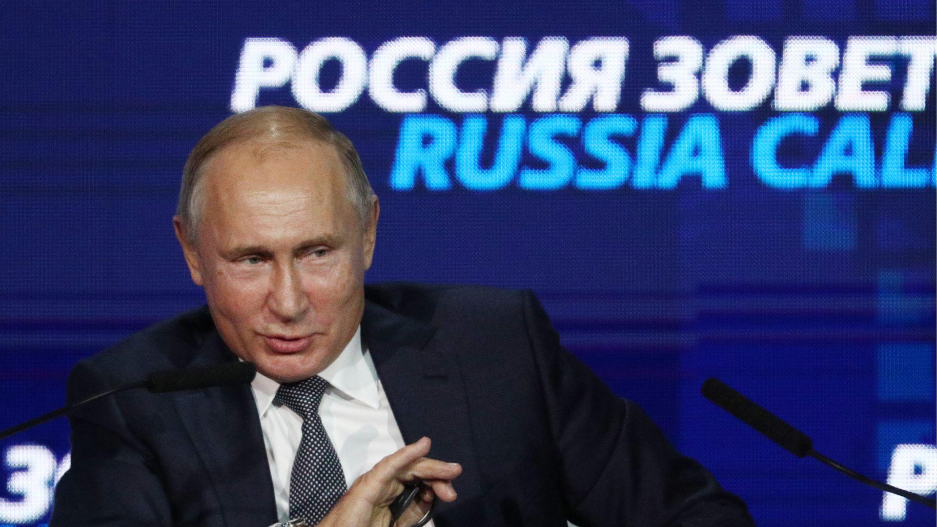 Vladimir Putin smiles and gestures.