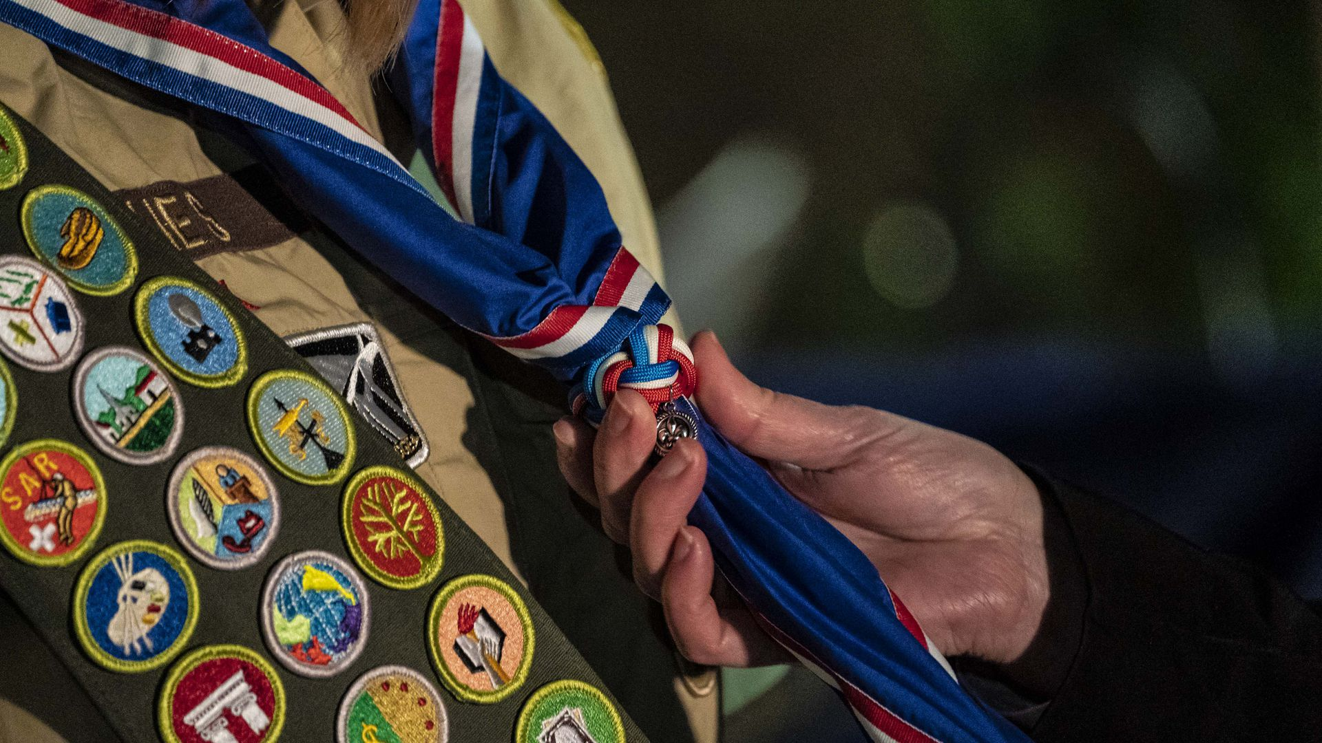 A photo a scout receiving a blue Eagle Scout neckerchief during a ceremony.