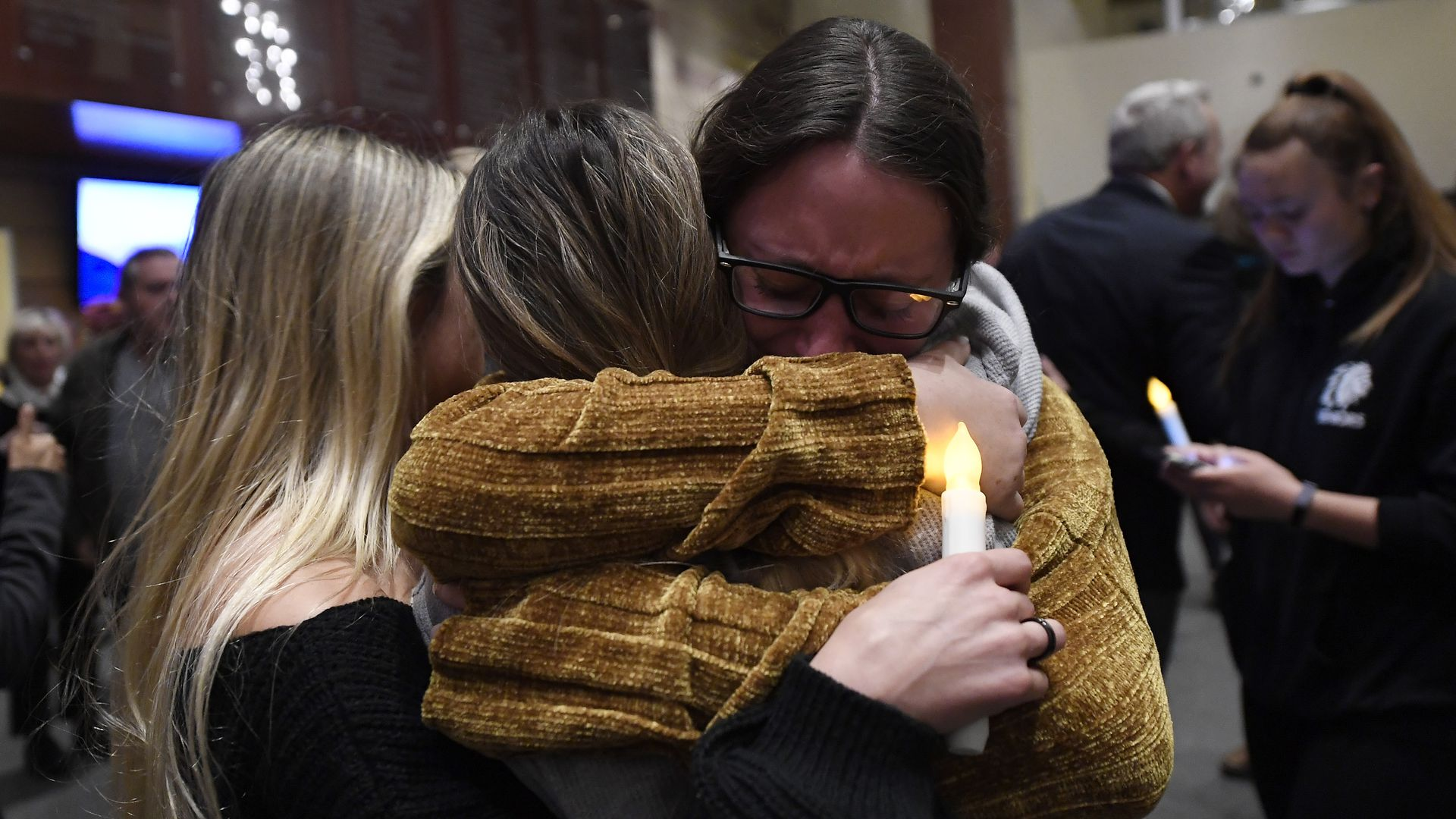 Mourners crying at a candle light vigil after the Thousand Oaks shooting