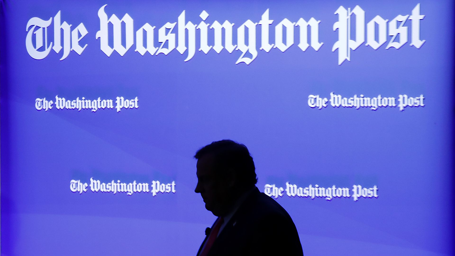 Silhouette of a man before wall with logos of The Washington Post.
