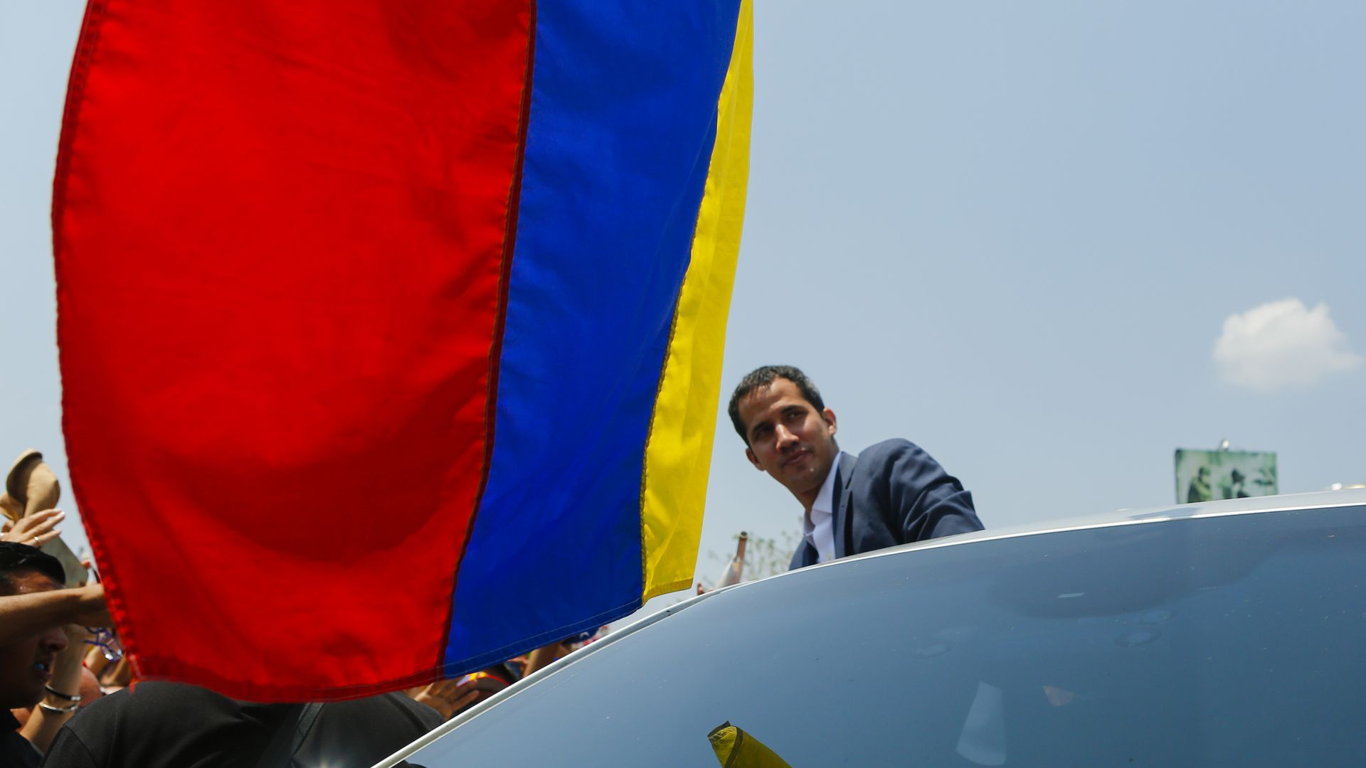 Juan Guaido stands next to a car with the Venezuelan flag hanging above him.
