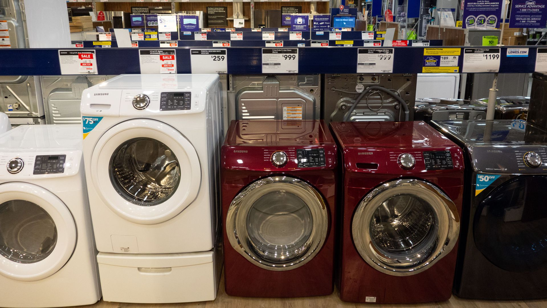 In this image, a row of different colors and brands of washing machines sit in a store.