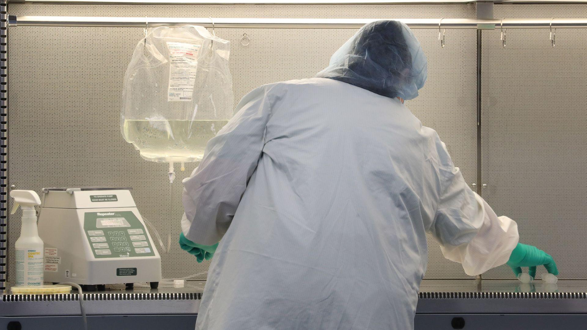 A pharmacy technician prepares an IV bag.