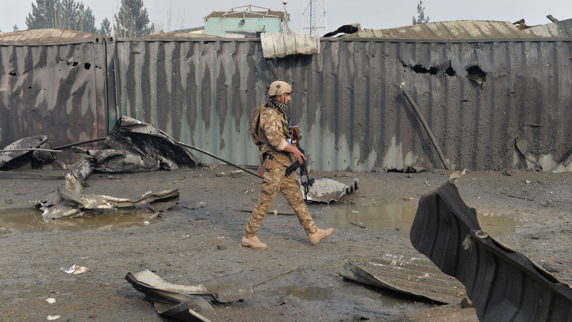 A member of the Afghan security forces walks at the site of a suicide bomb attack outside a British security firm's compound in Kabul, a day after the blast on November 29, 2018.