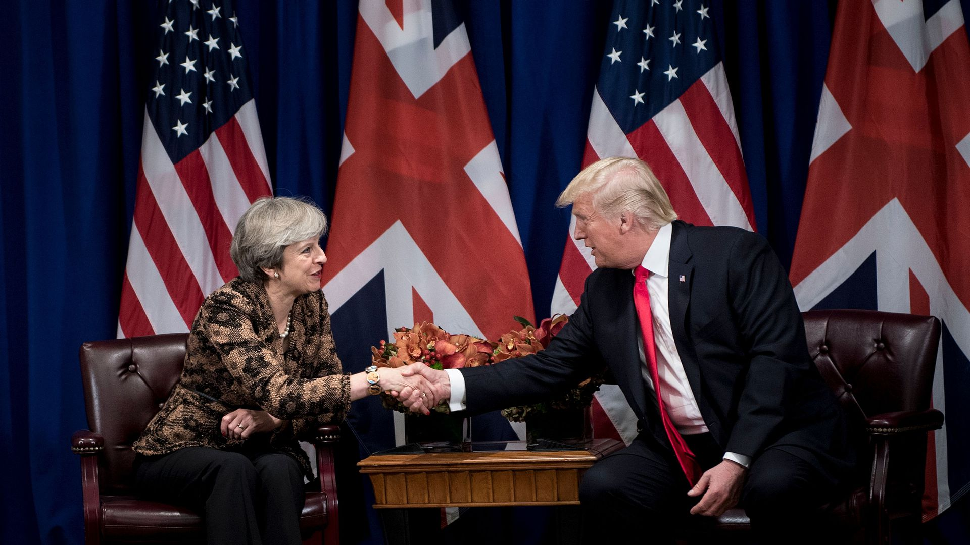Theresa May and Donald Trump shaking hands.