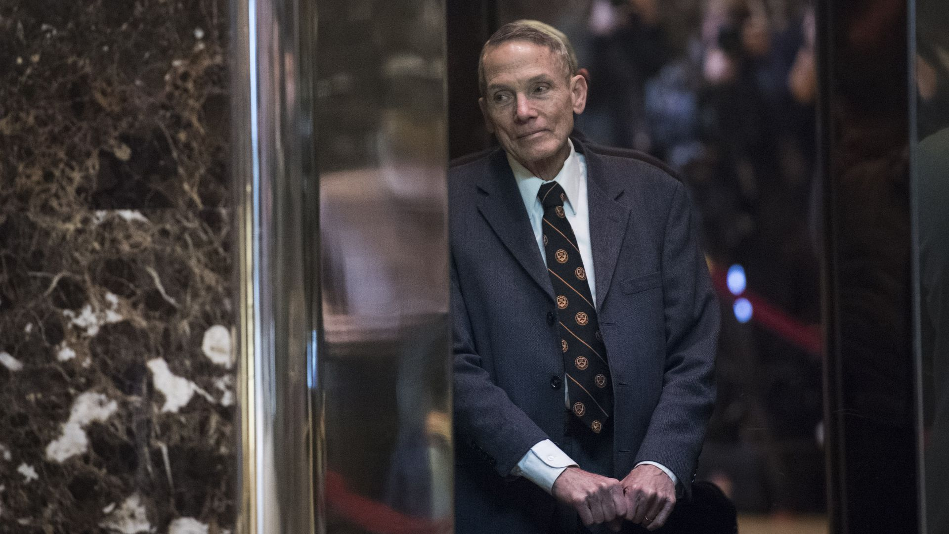 In this image, William Happer leans against a marble wall. He's wearing a gray suit and a black and orange striped tie.
