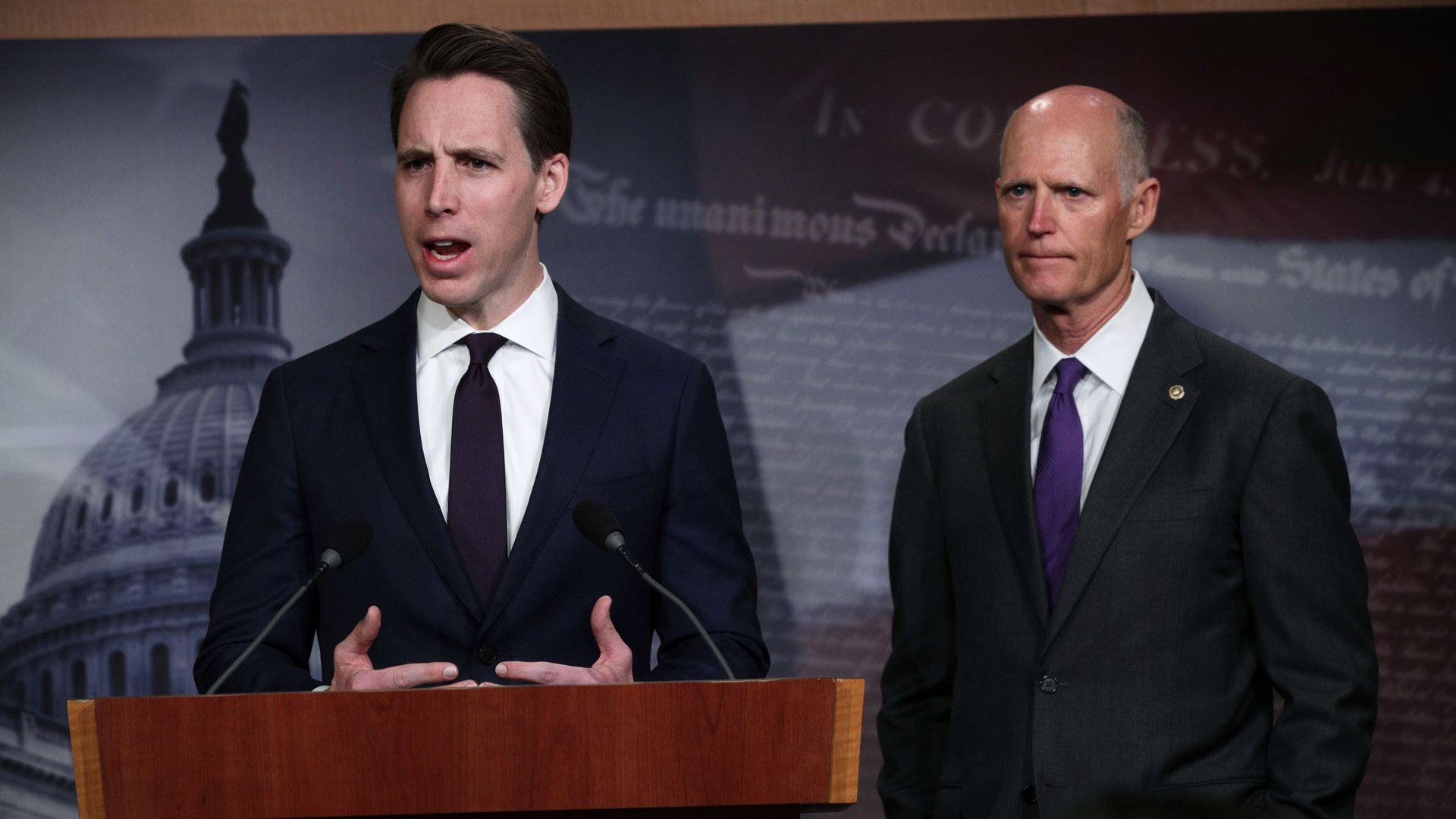 U.S. Sen. Josh Hawley speaks from behind a podium as Sen. Rick Scott stands next to him and listens.