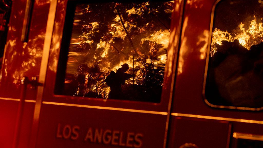 Image of the raging fires are reflected on windowpane of firetruck in Los Angeles