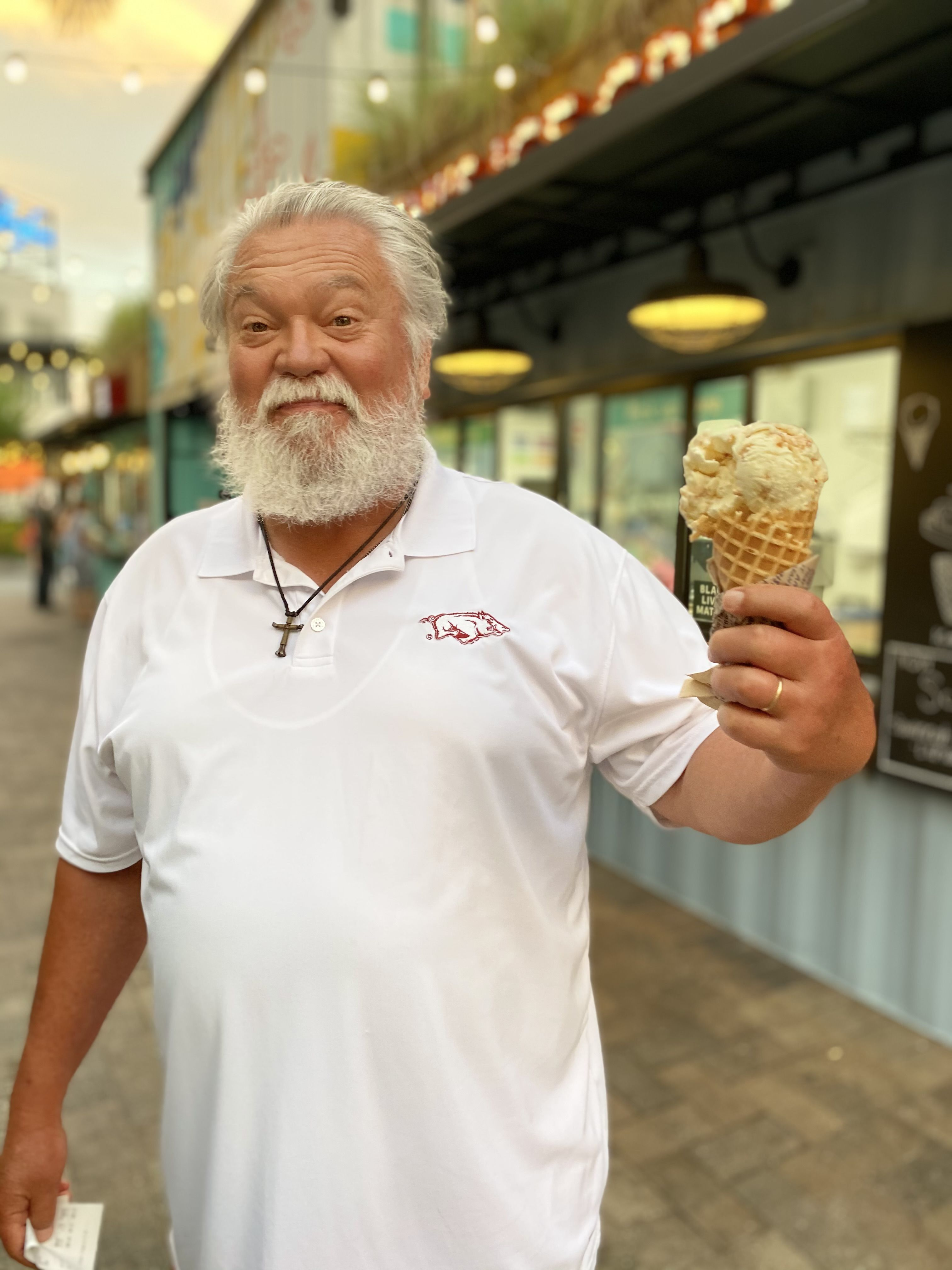 A tall man with white hair is holding and an ice cream cone.
