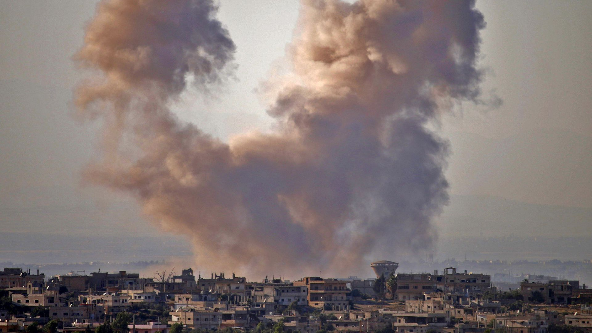 smoke rising over town of Daraa, Syria, after an airstrike