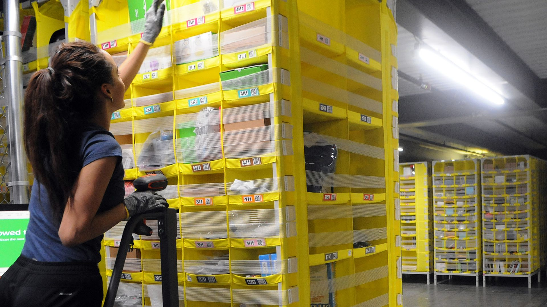A woman reaches for an item on a yellow shelf in a warehouse