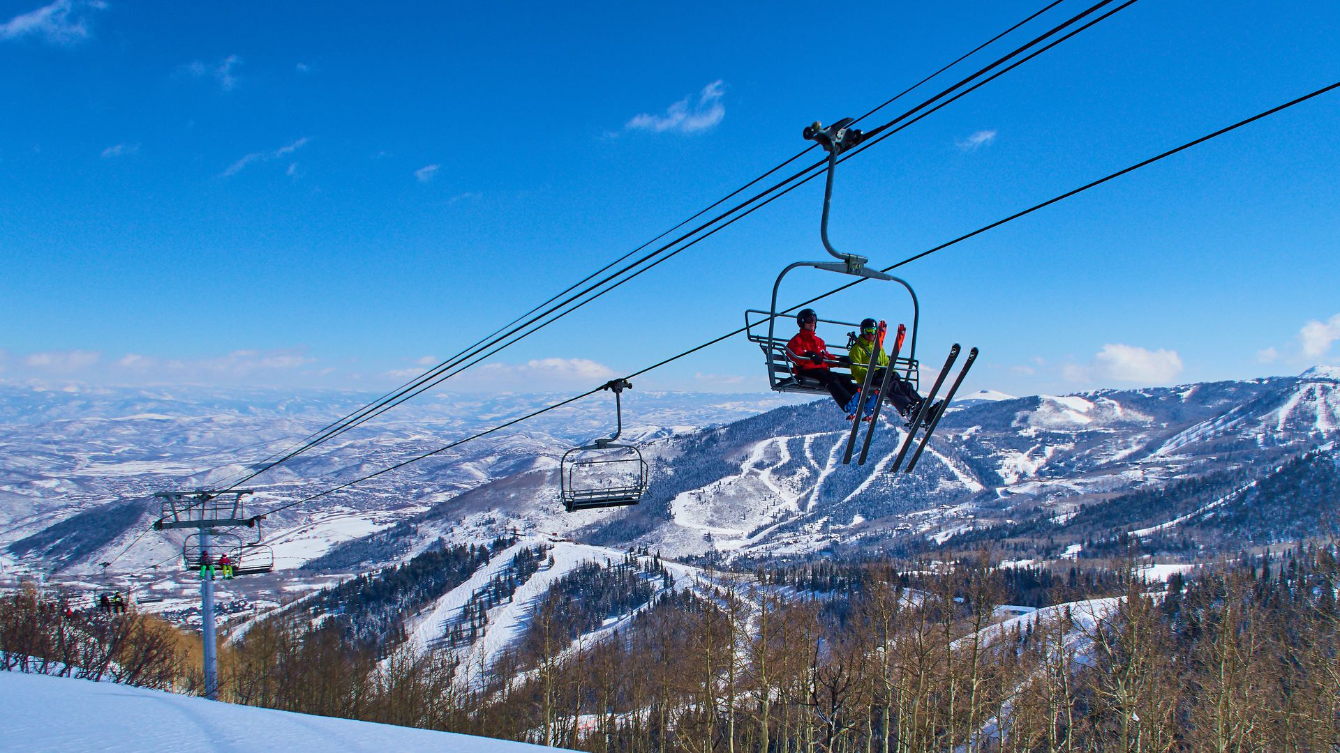Skiers are sitting in a chair lift with panoramic view of the Wasatch Range in the Rocky Mountains on March 02, 2015 in Park City, Utah, United States.