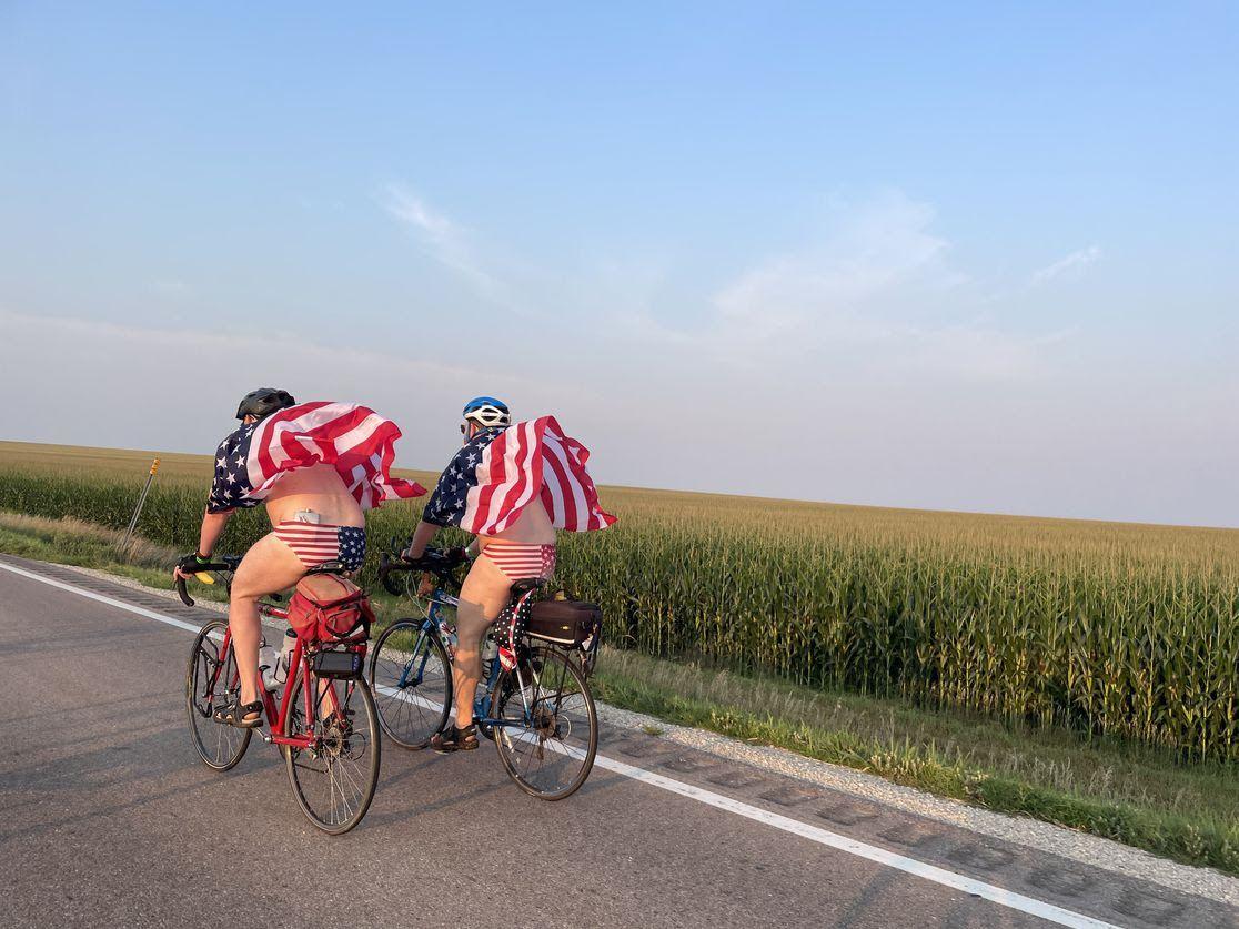 Two men wear matching American flag speedos and shirts while biking for RAGBRAI.