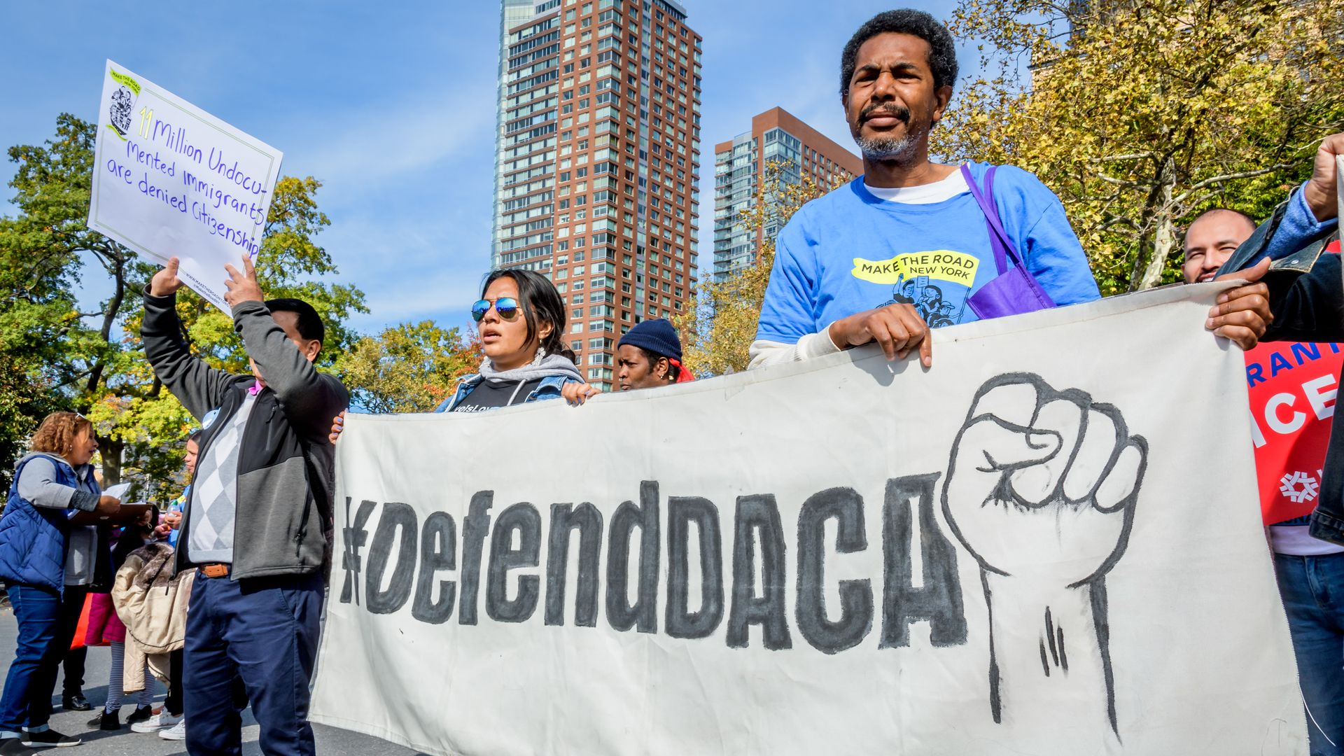 "Protestors hold signs saying ""Defend DACA"""