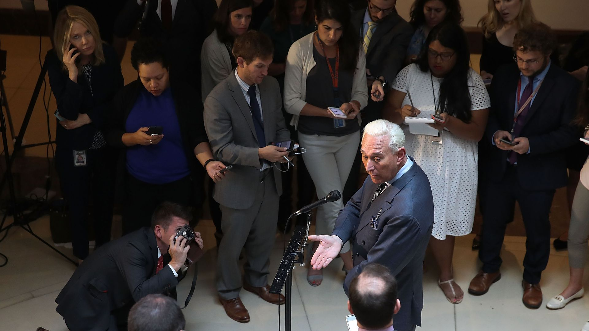 Stone surrounded by reporters at the Capitol