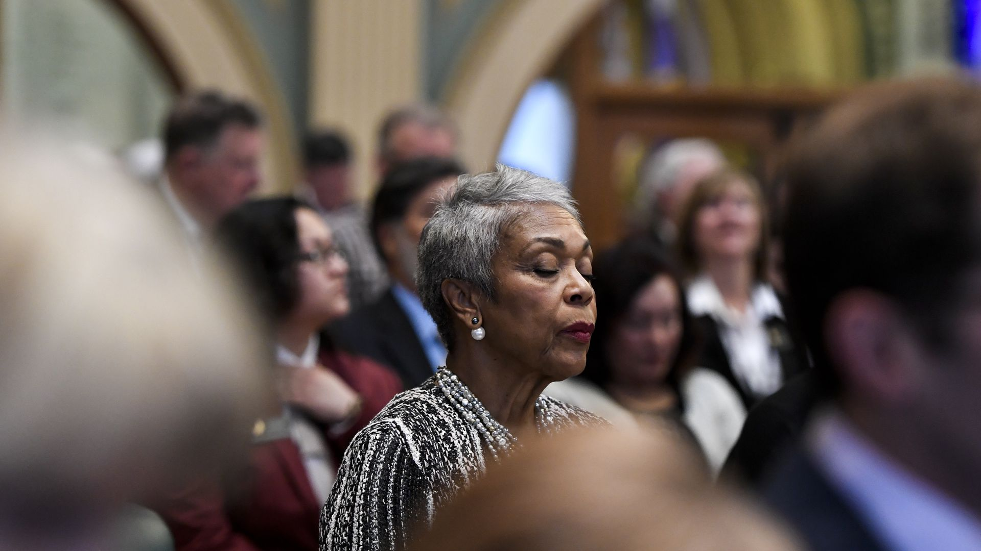 State Rep. Janet Buckner stands on the House floor with her eyes closed.