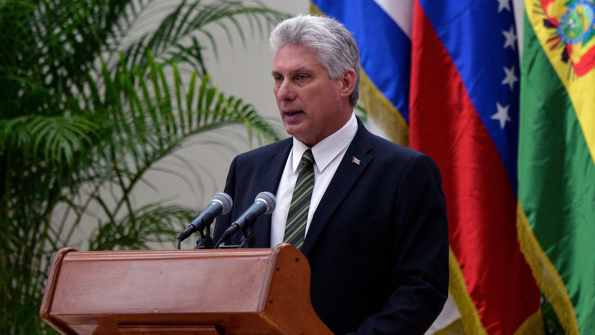 Miguel Diaz-Canel speaking at a lectern in front of Cuban flag