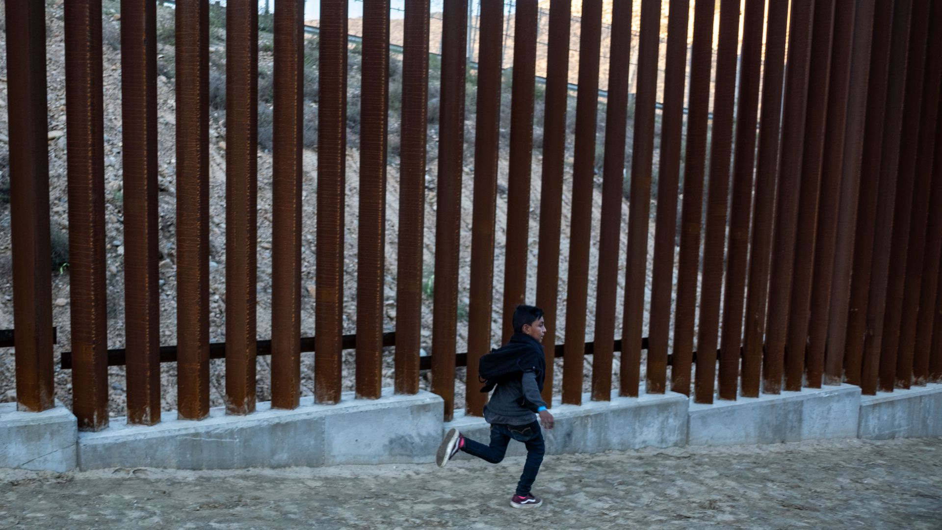 Boy runs near border wall.
