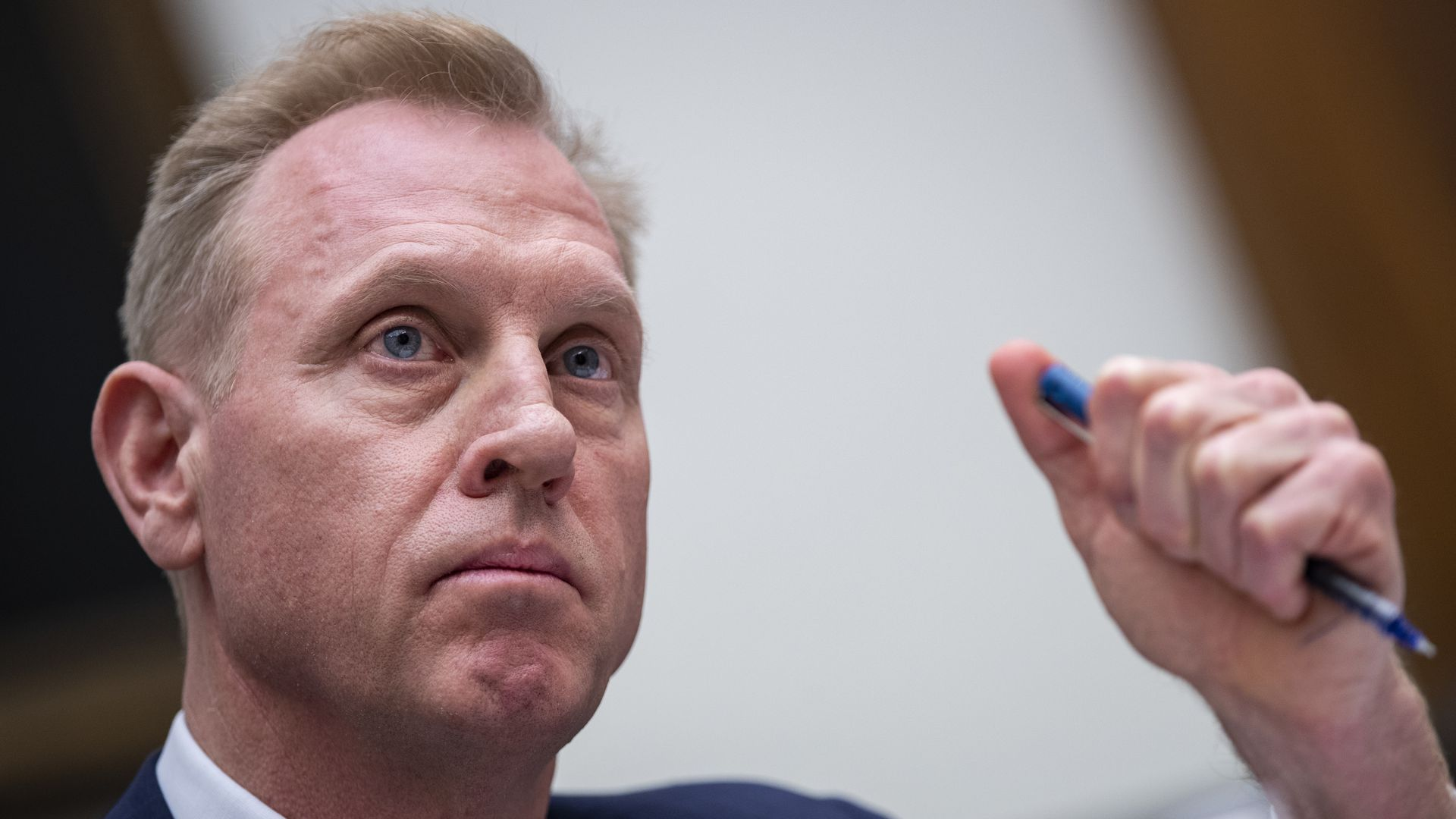 In this image, Patrick Shanahan sits and frowns while holding a pen in his fist.
