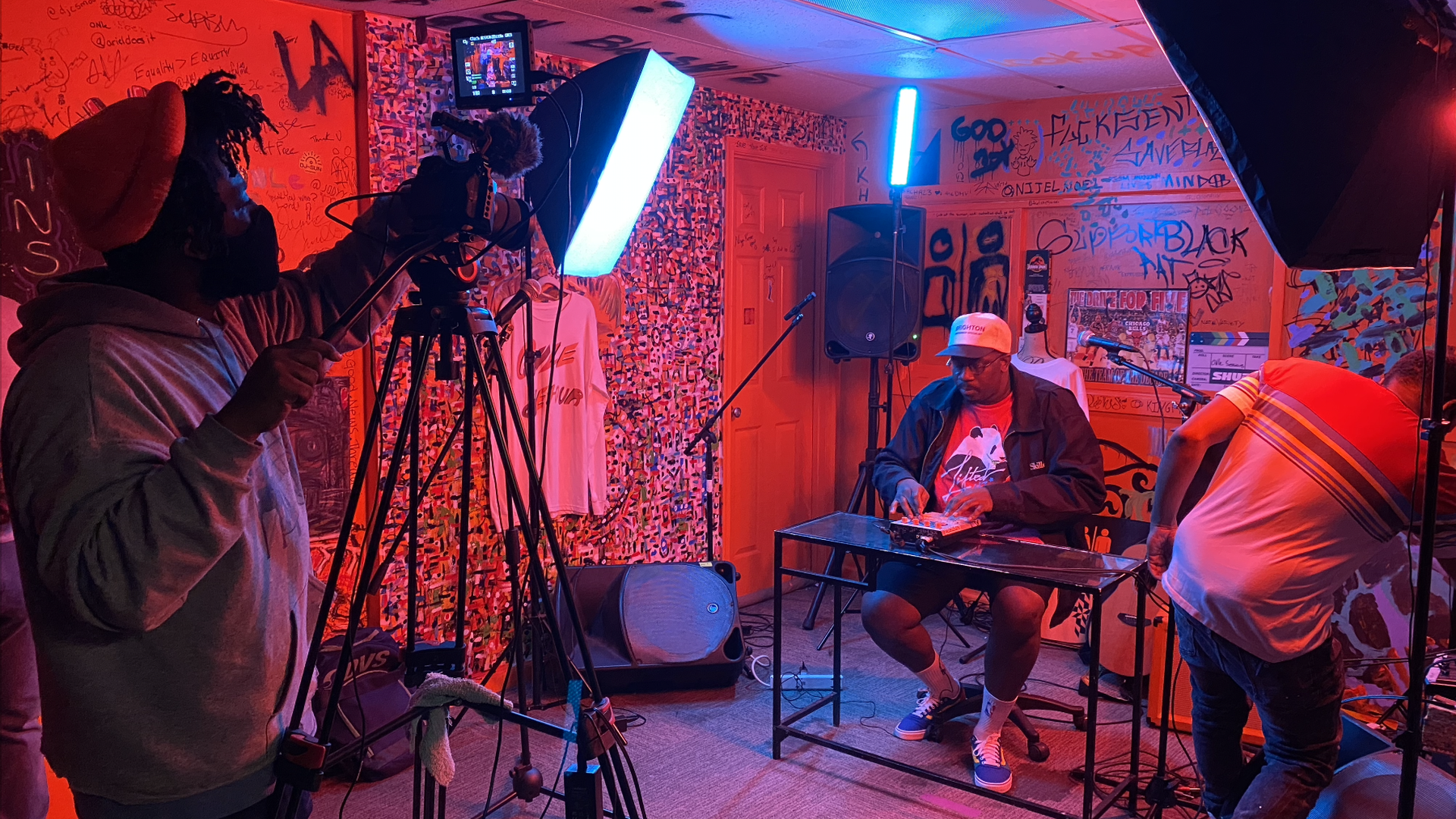 A man operates a camera as a musician plays an electronic sound board under red/orange lighting.