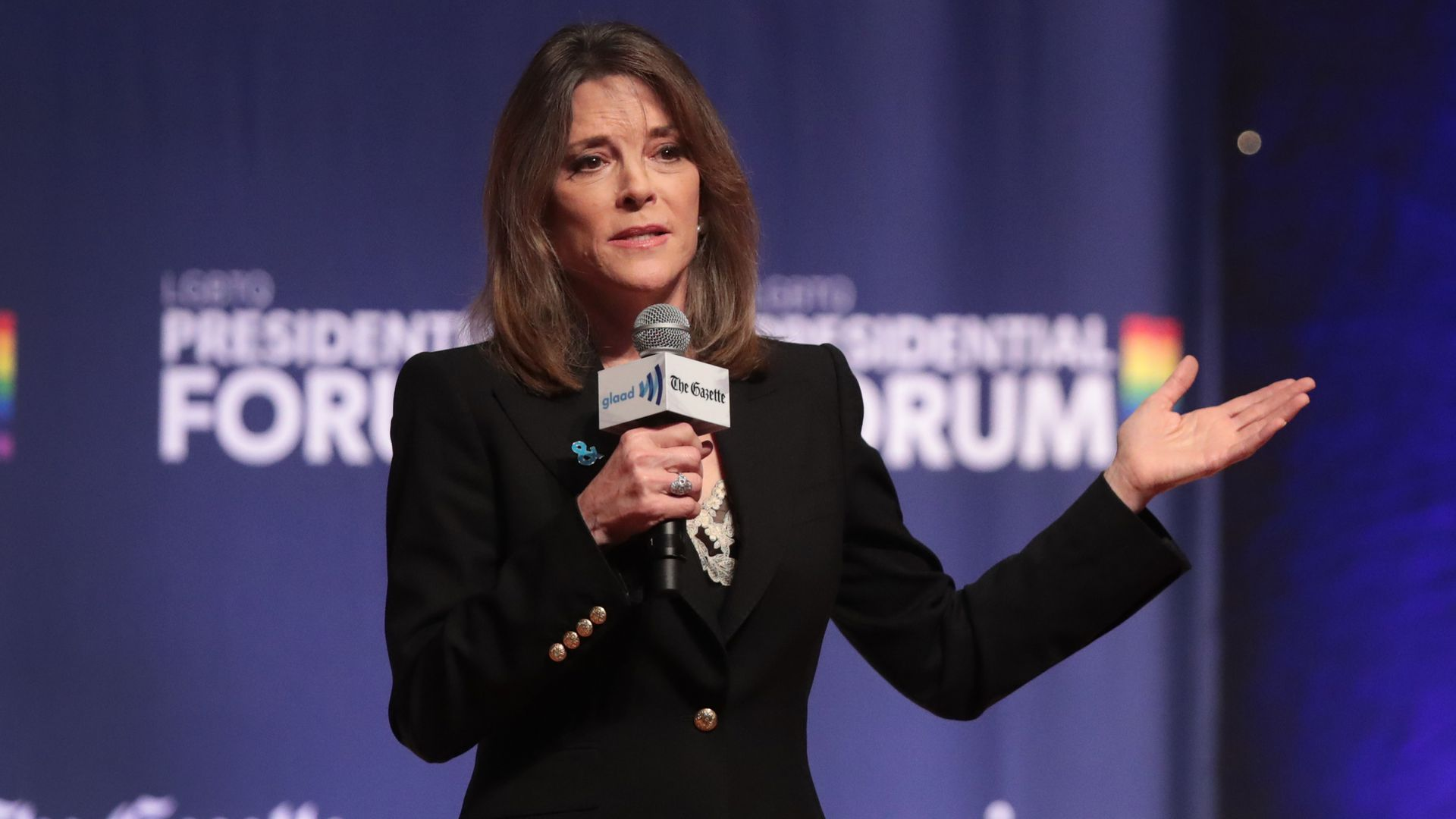 Marianne Williamson holds a microphone.