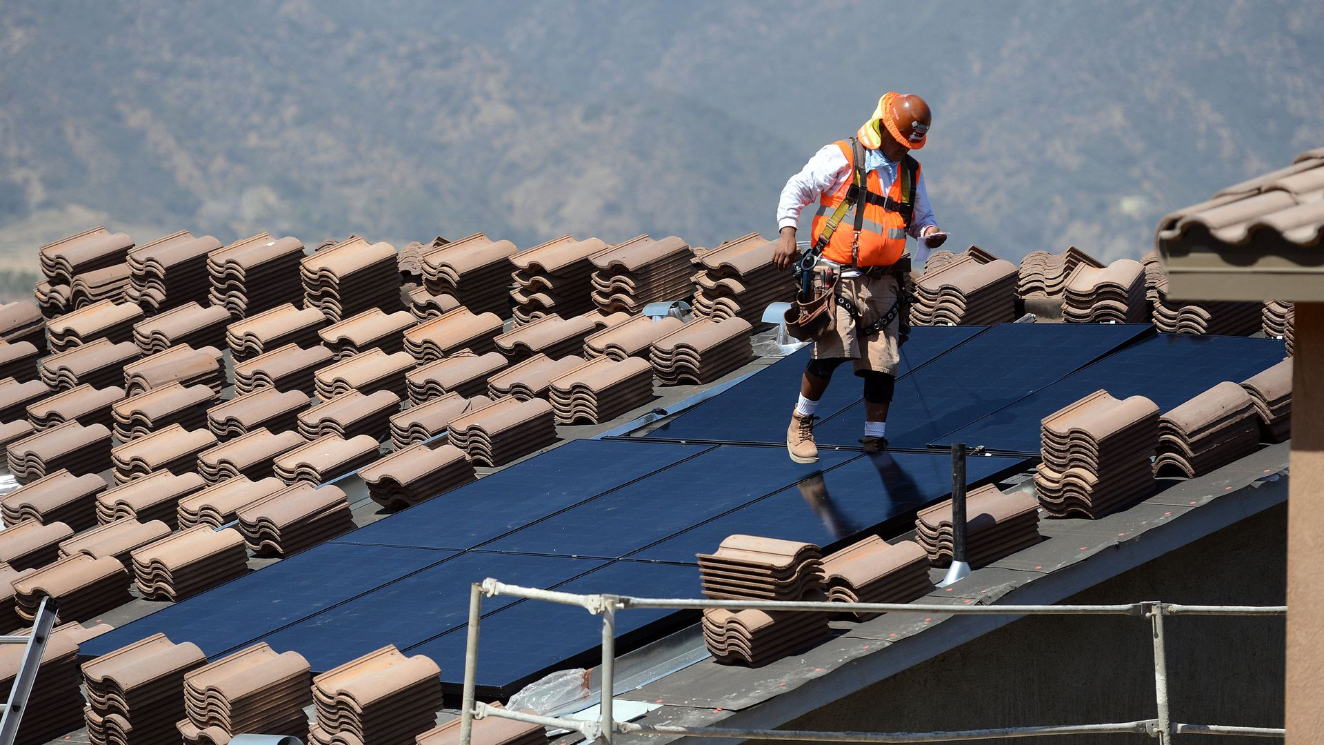 Workers install solar panels on the roofs of homes under construction south of Corona on May 3, 2018.