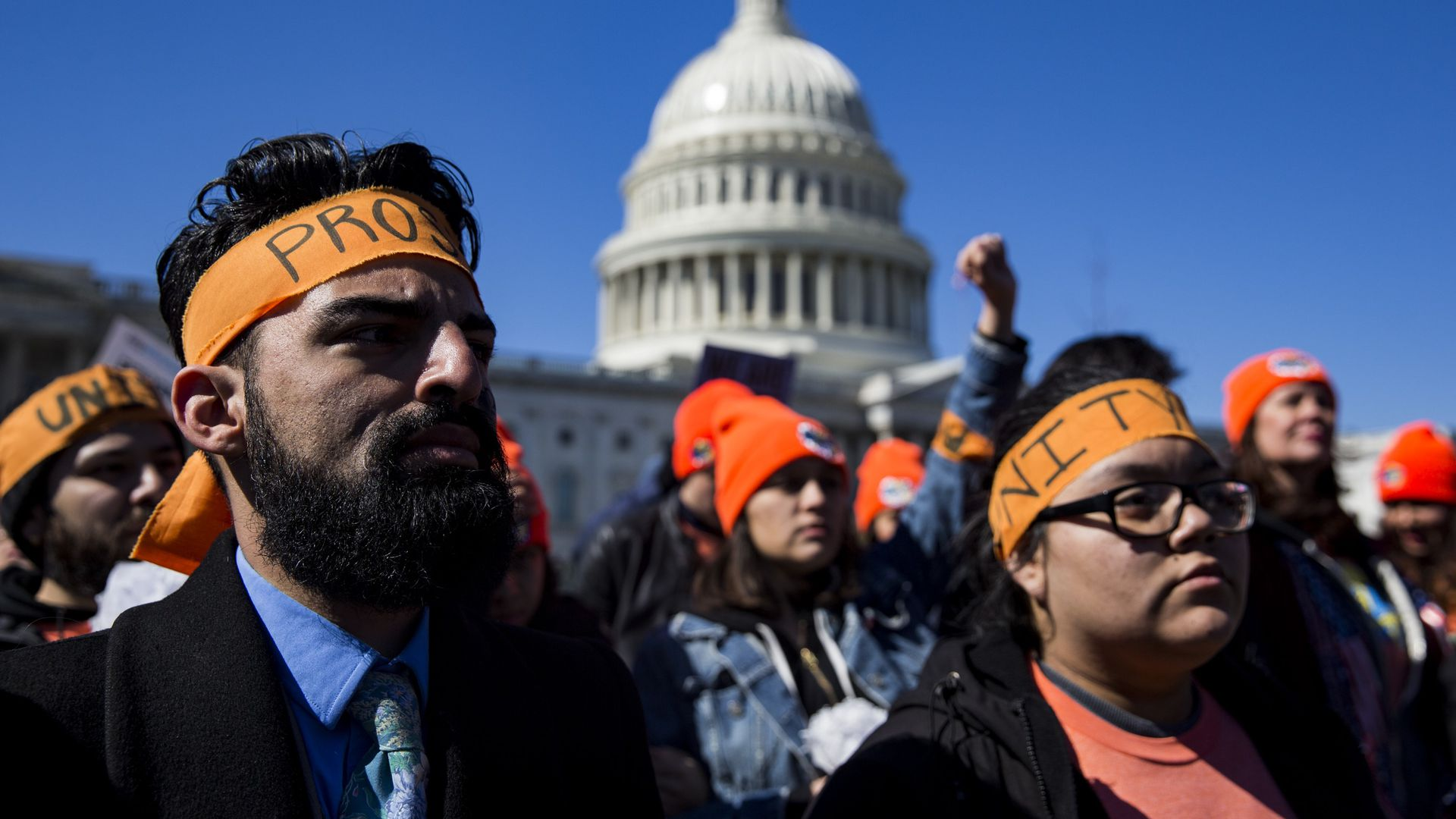 DACA protestors wearing orange headbands out front of the U.S. Capitol building