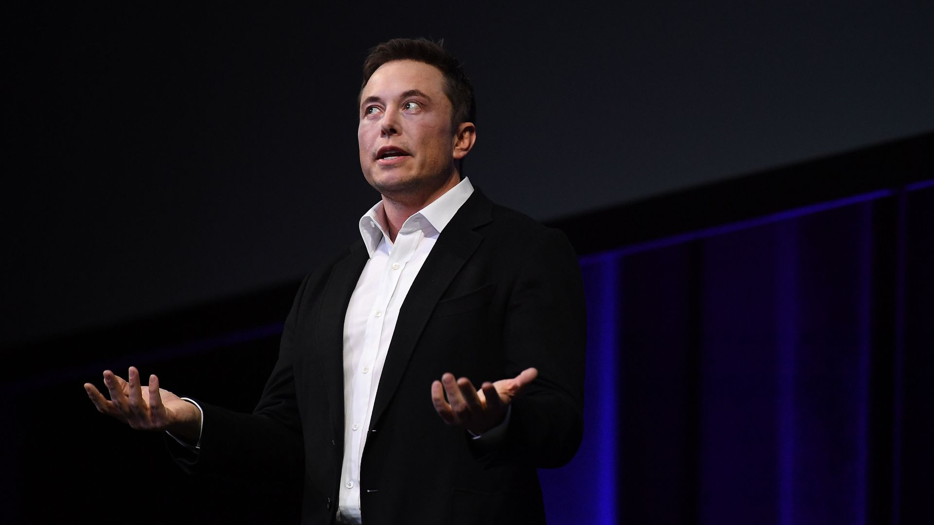 Elon Musk in a black suit, white shirt and no tie with both hands palms up talking